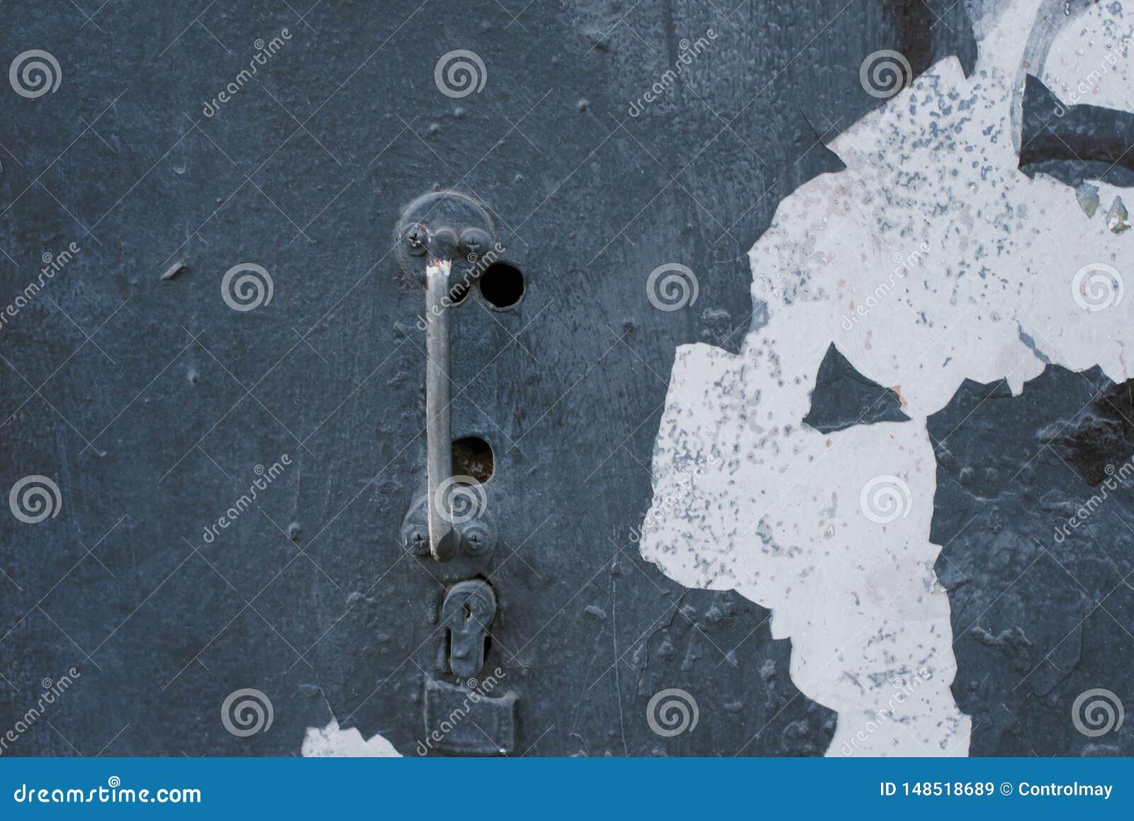 Gammalt rostigt slankt handtag på en retro dörr