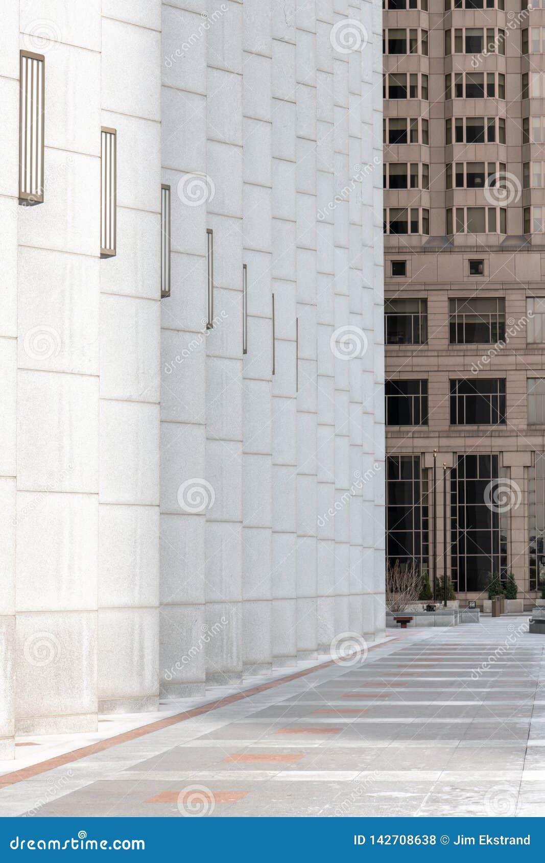 Gang en kolommen met lijnen die tot perspectief tussen bureaugebouwen leiden in het stedelijke plaatsen - verticale richtlijn