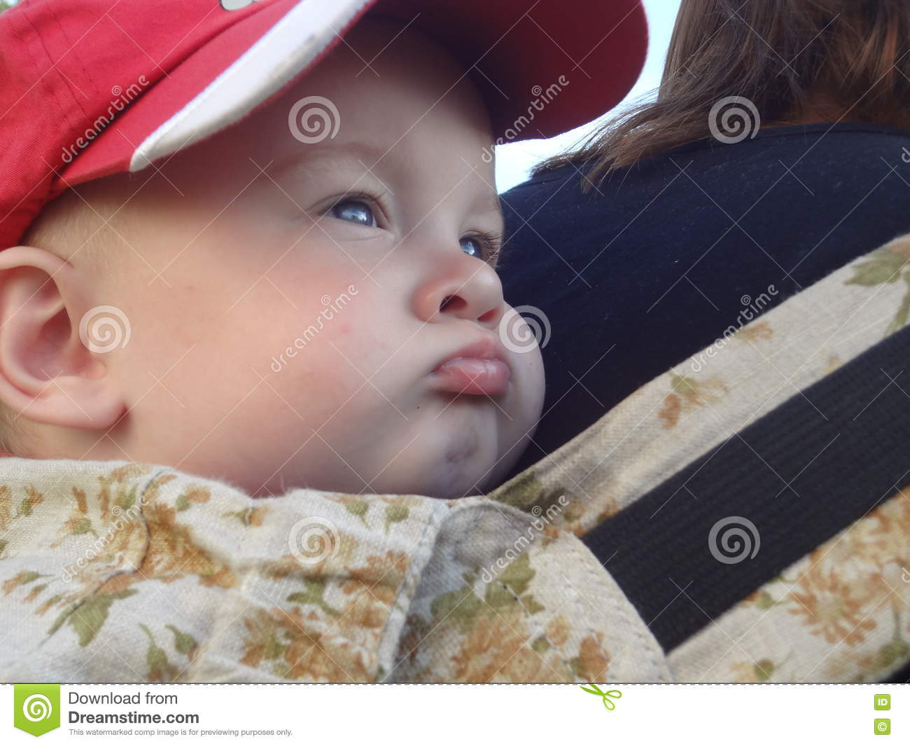 87f625717275f Gangster baby boy with lips and cheeks on mother's back Frowned baby in in red  cap looks like gangster or rap music artist.