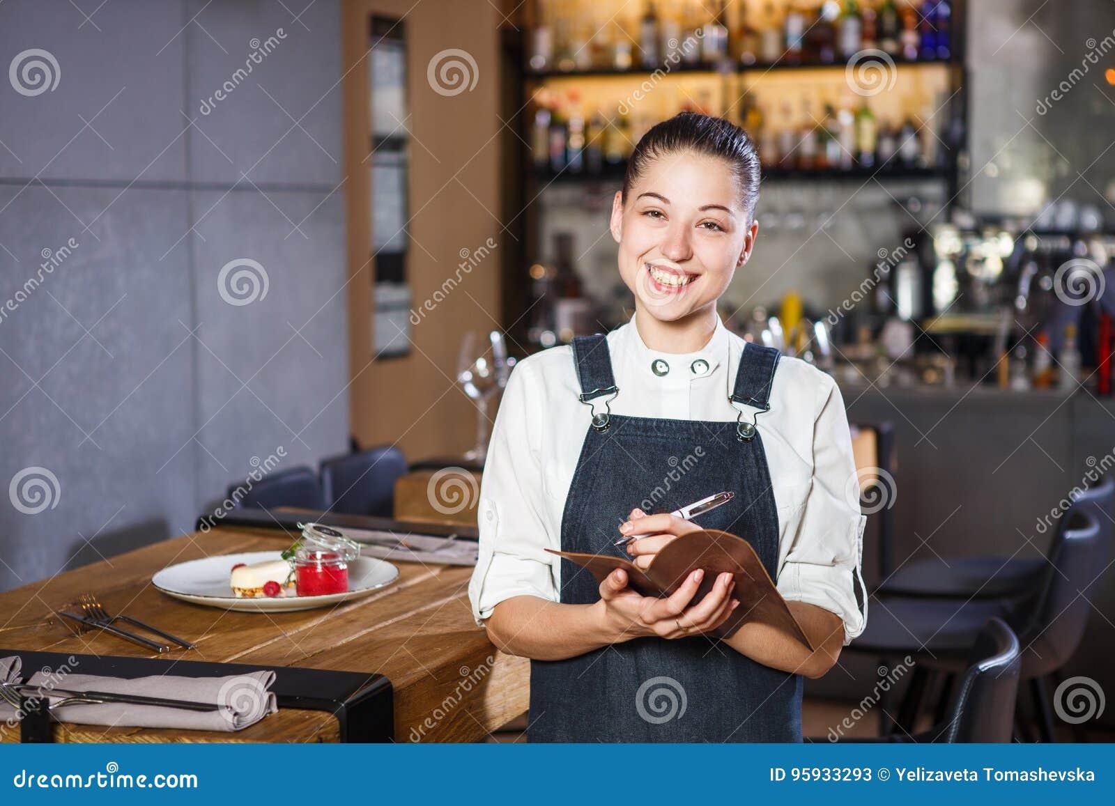 Ganson, de ambtenaren, mooie deushka met een glimlach en het verzamelde haar in werkende vormschort keuren een orde in restaurant