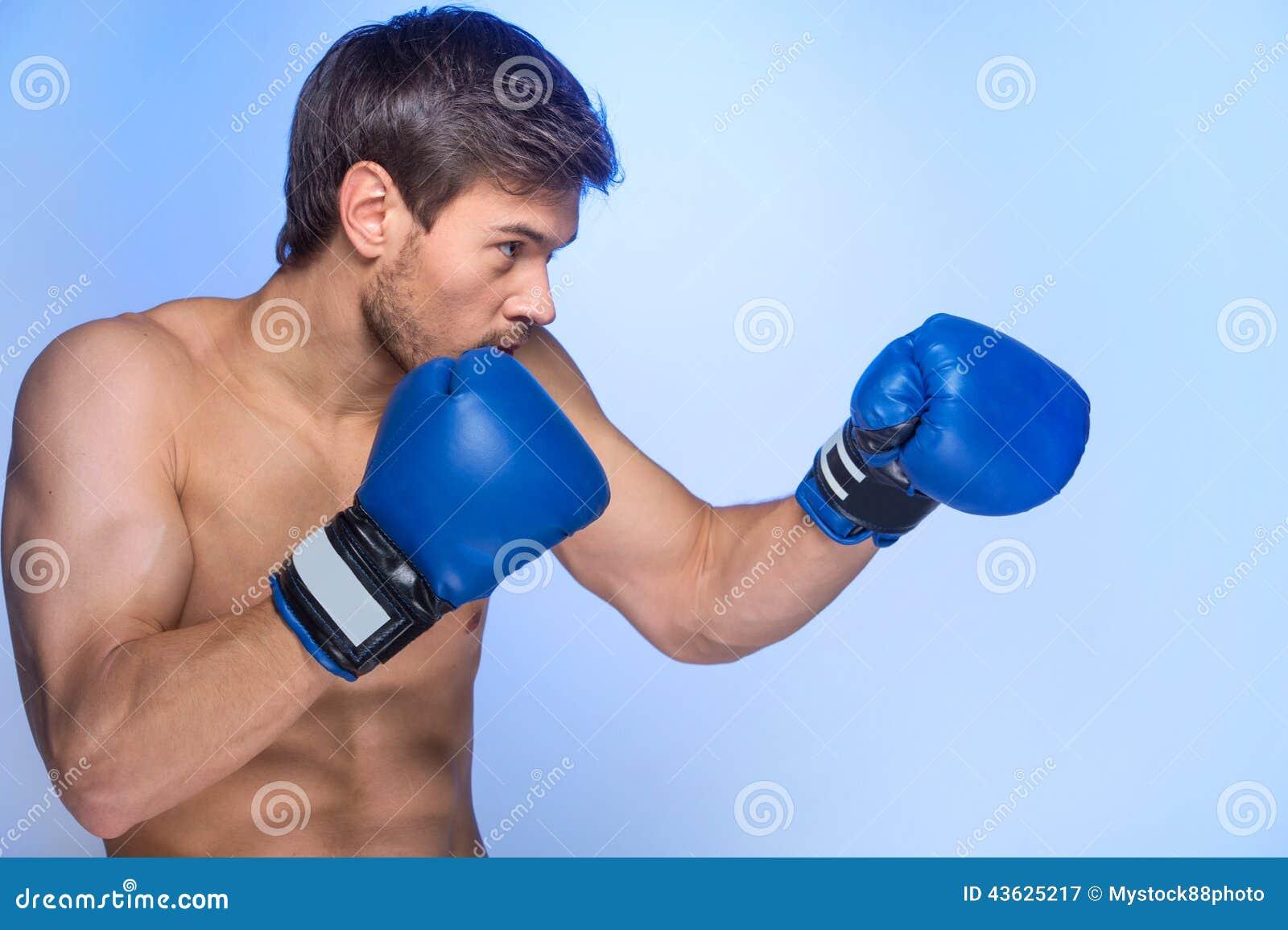 Gants de boxe de port de jeune homme musculaire beau