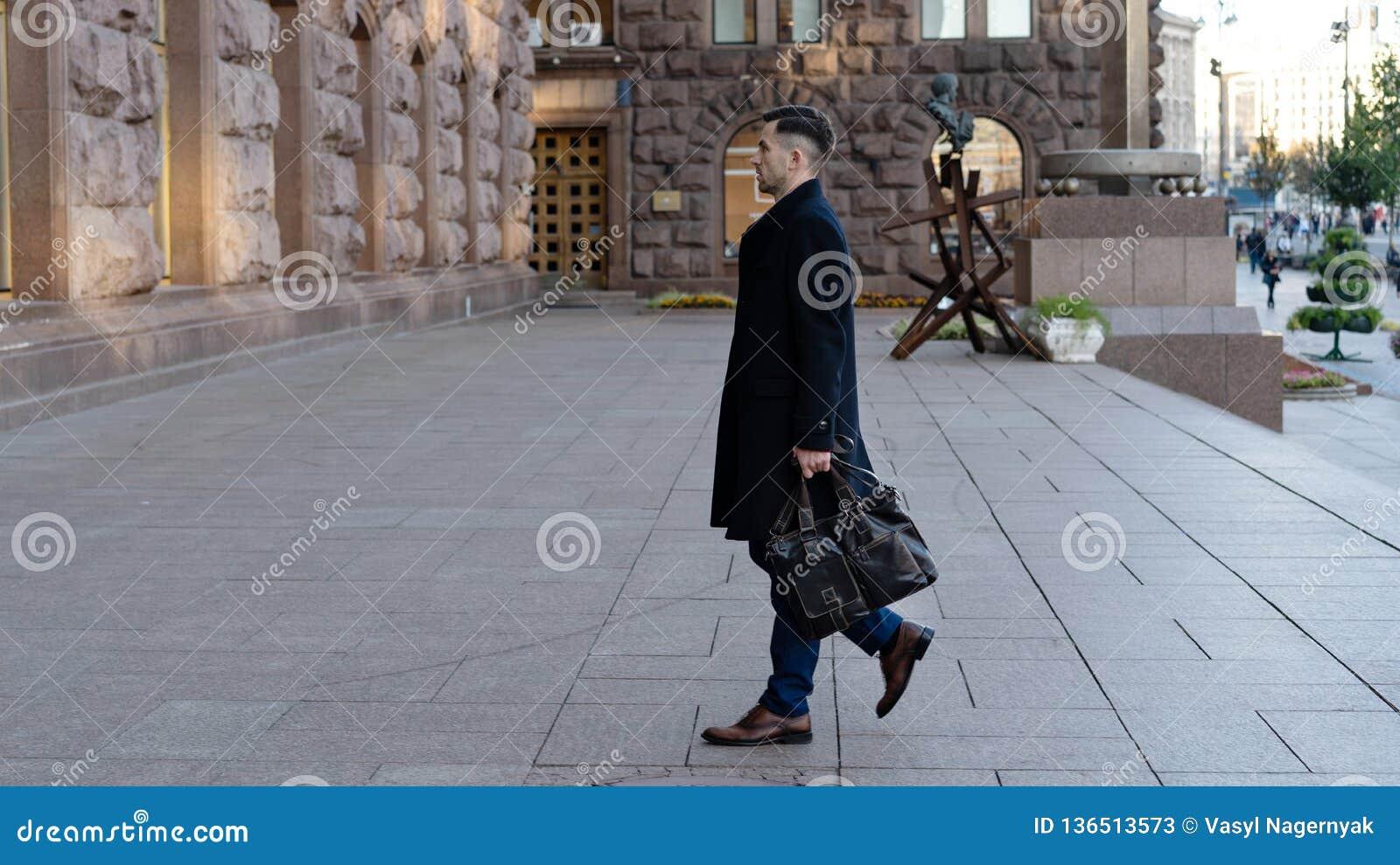 Ganzaufnahme eines überzeugten jungen Geschäftsmannes, der in die Stadt mit einer Tasche geht