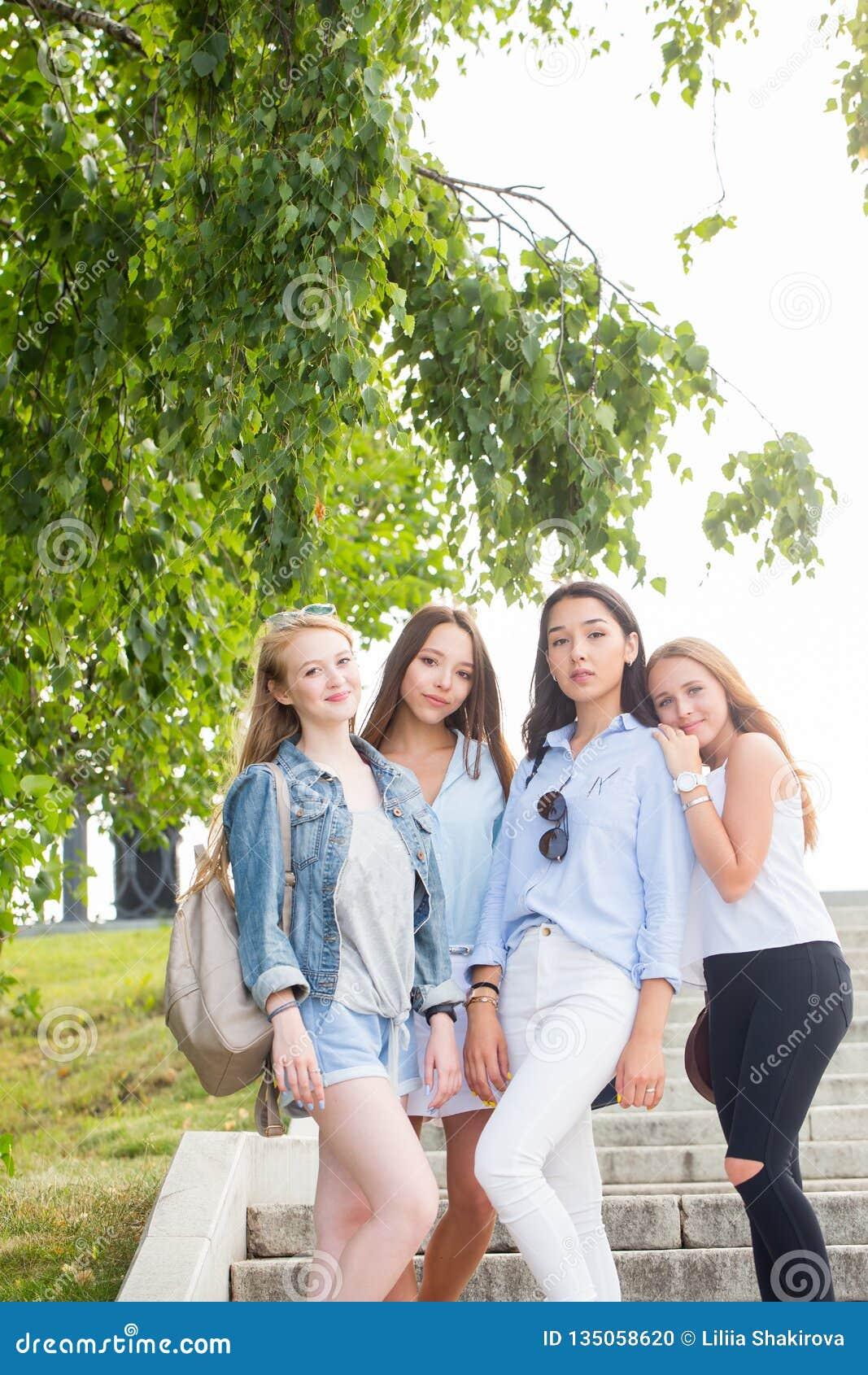 Ganzaufnahme von reizend jungen Studentenmädchen im Park im Sommer Frauenabnutzungspastell färbte Kleidung, Turnschuhe und Schuhe