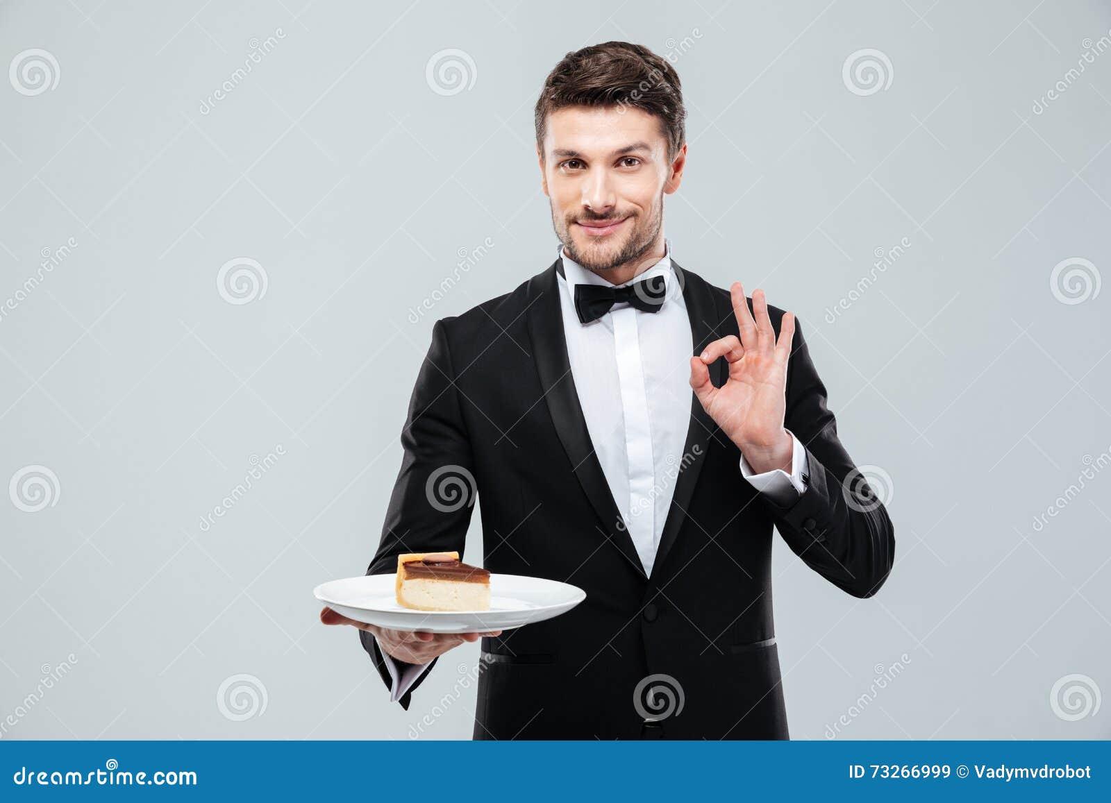 Garçom que guarda a placa com bolo e que mostra o sinal aprovado