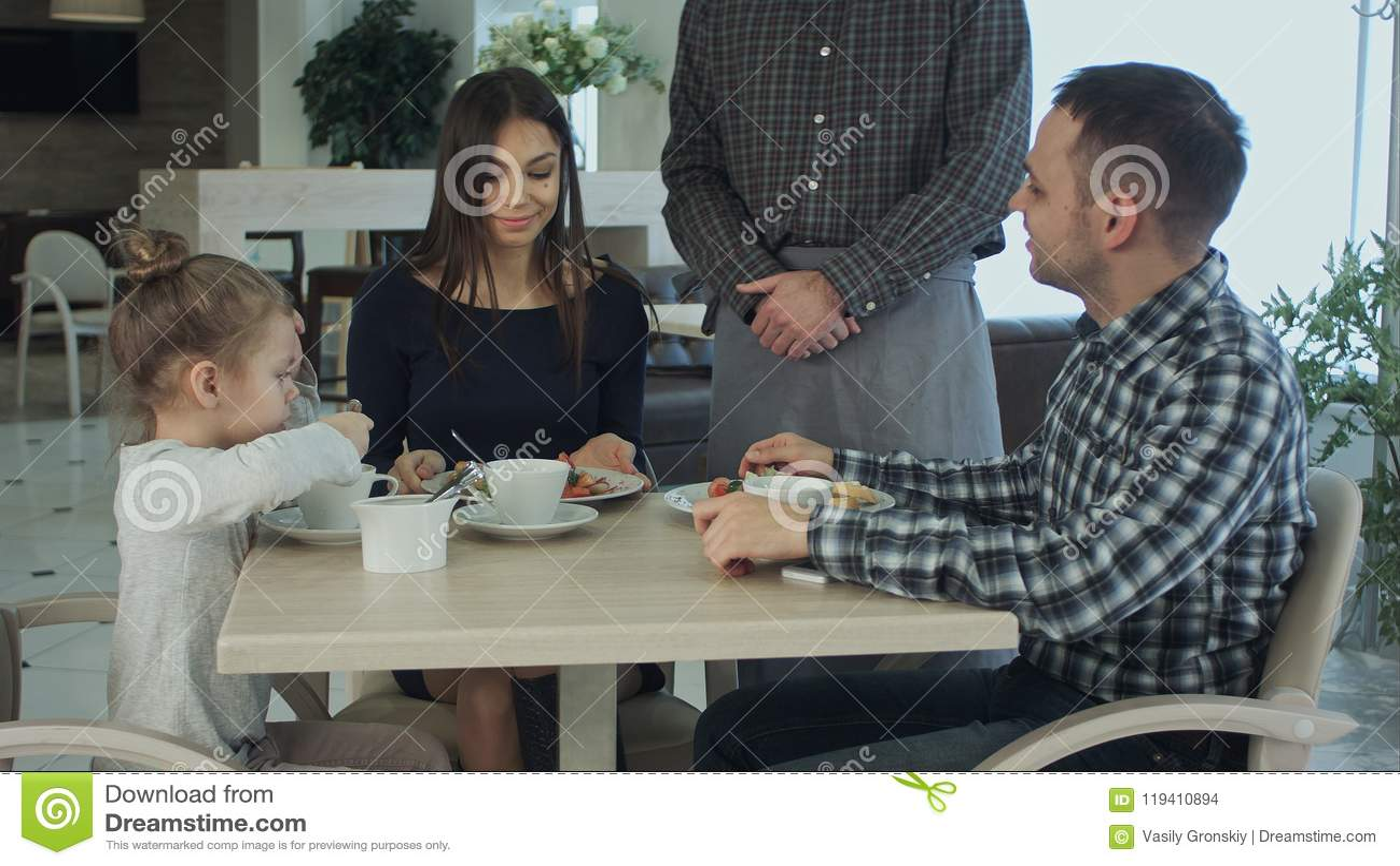 Garçom que toma a ordem na tabela da família que tem o jantar junto Eles que olham felizes e satisfeitos