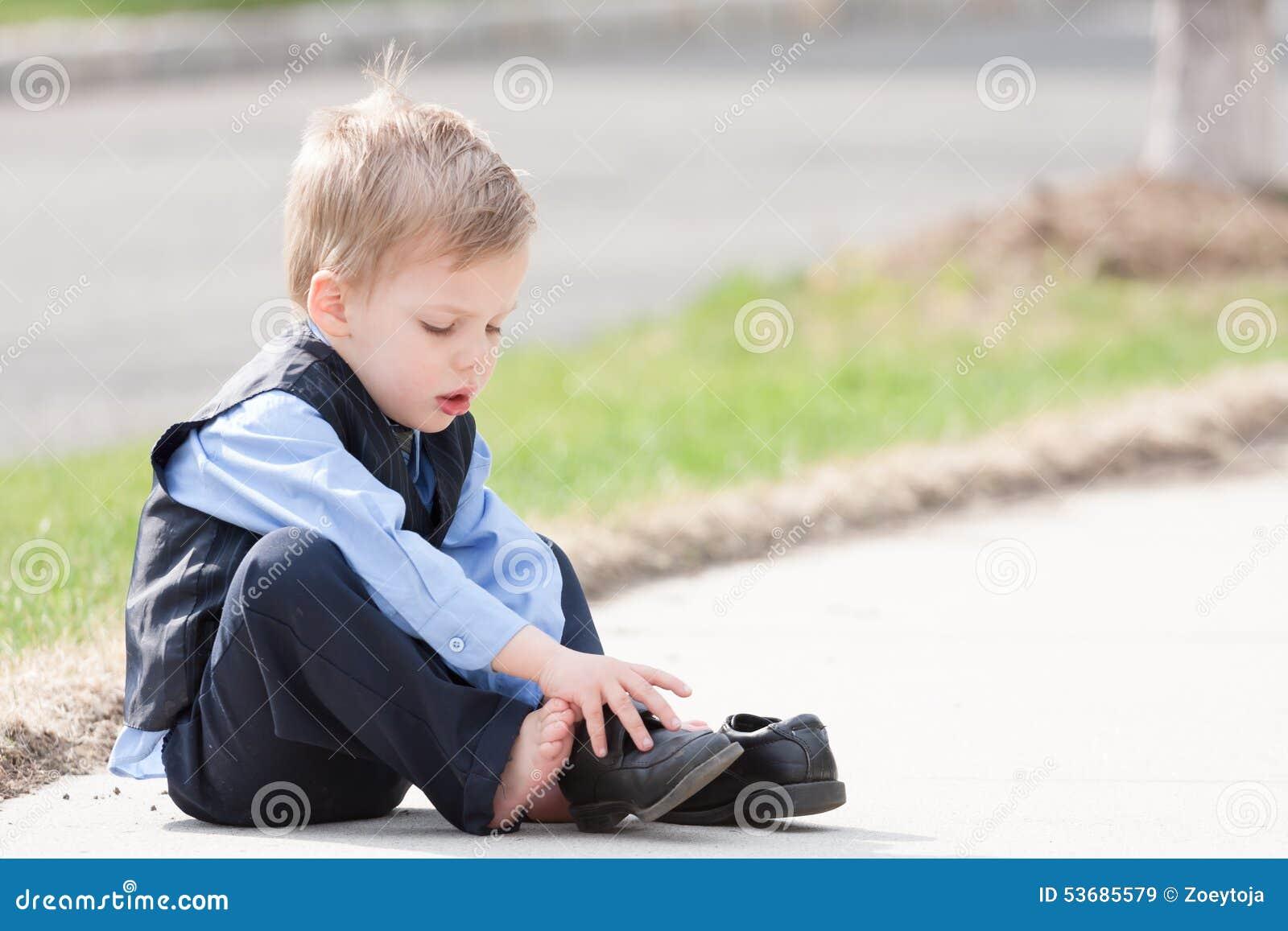 420550f5856b54 Garçon adorable d enfant en bas âge essayant de mettre ses chaussures dessus