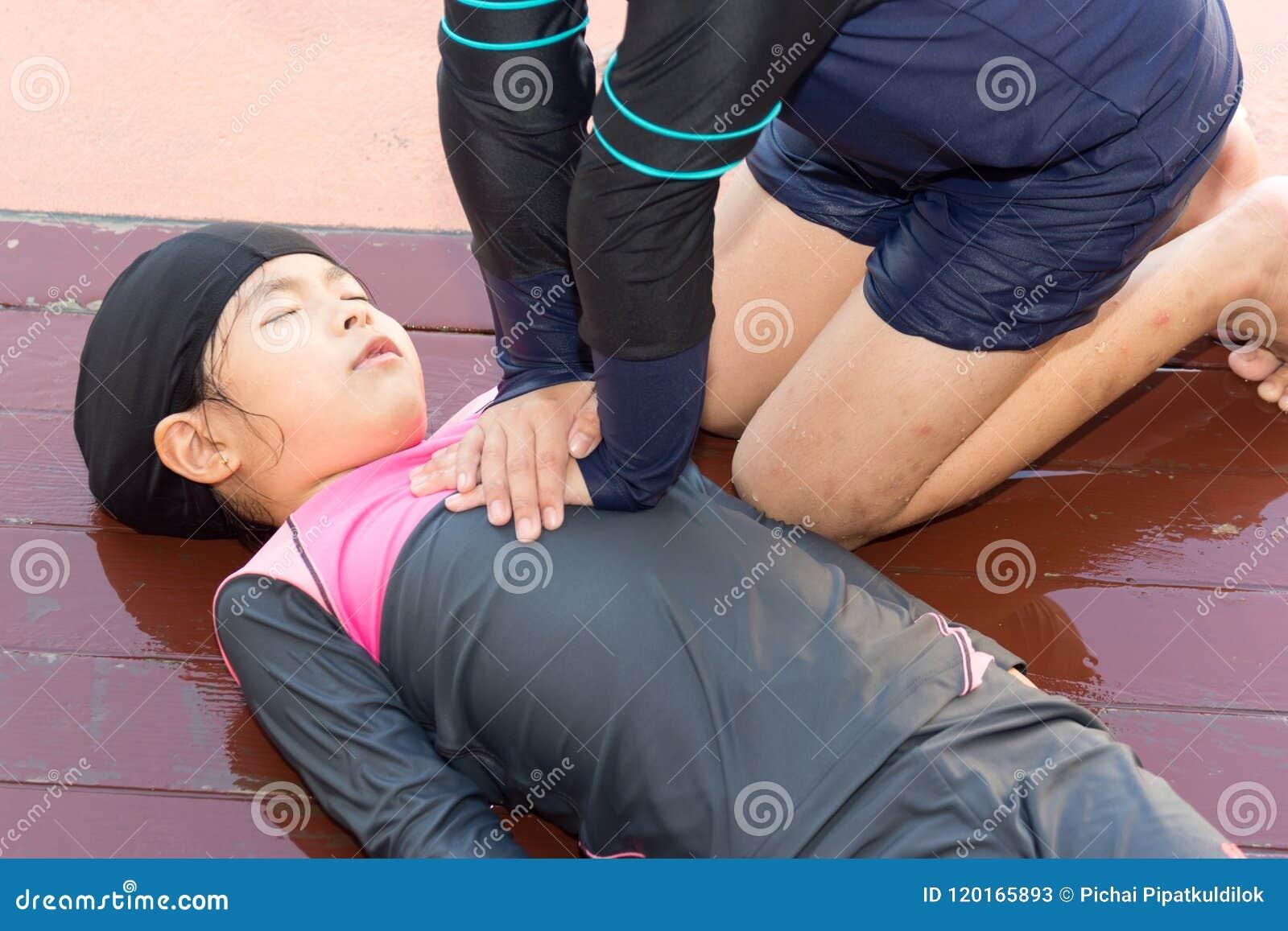 Garçon aidant noyant la fille d enfant dans la piscine en faisant le CPR
