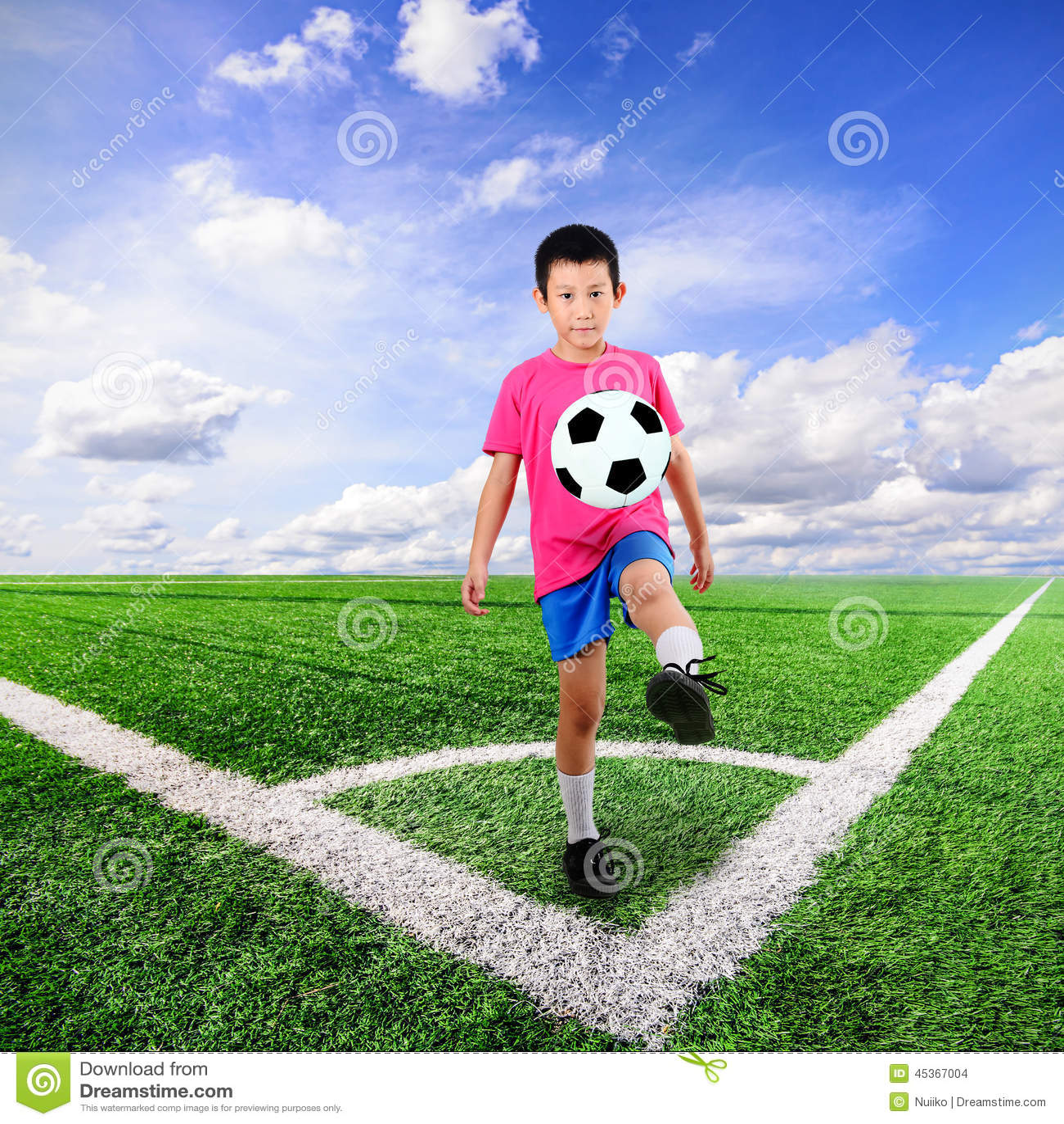 Garçon asiatique avec du ballon de football au terrain de football