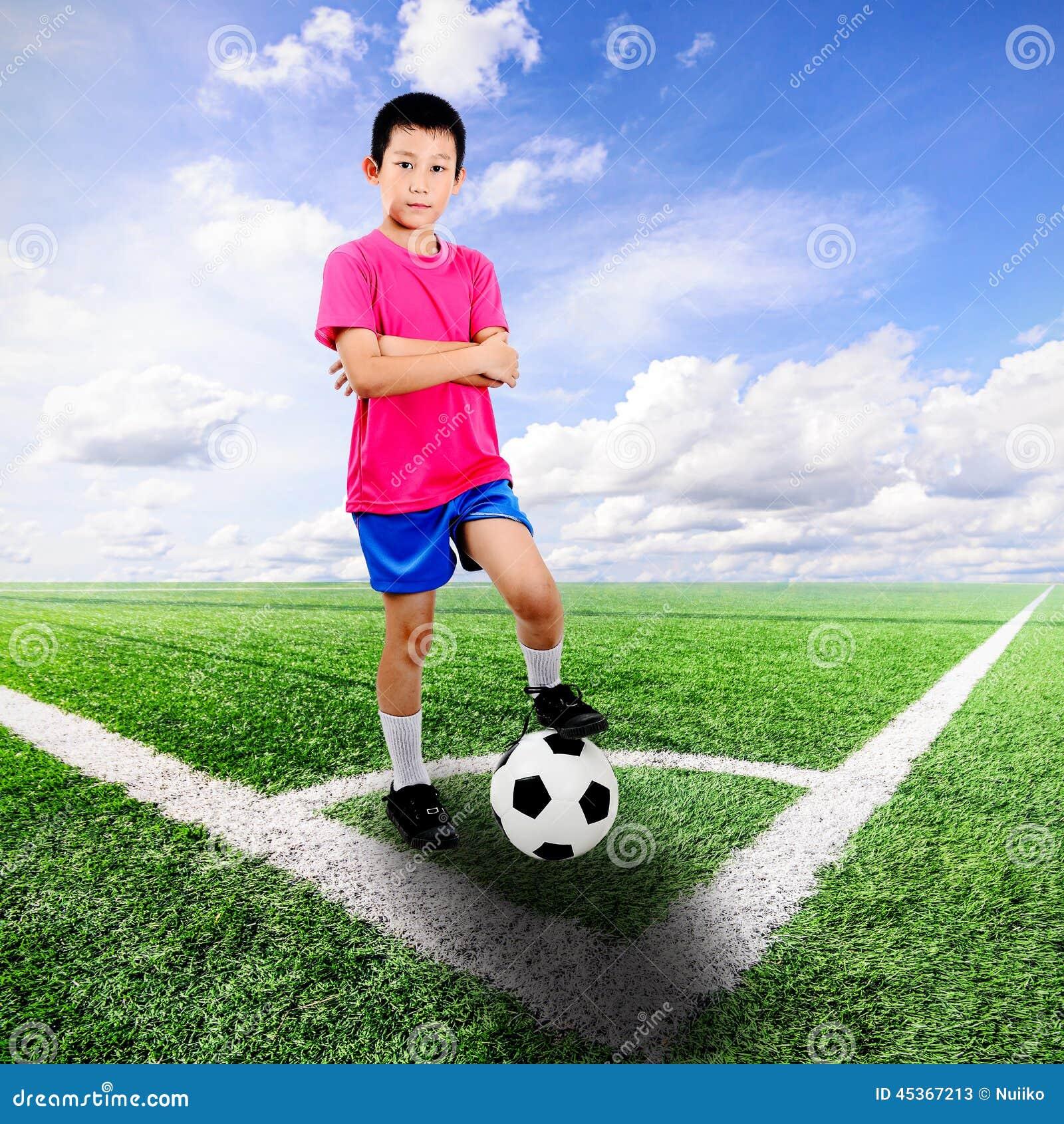 Garçon asiatique avec du ballon de football sur le terrain de football