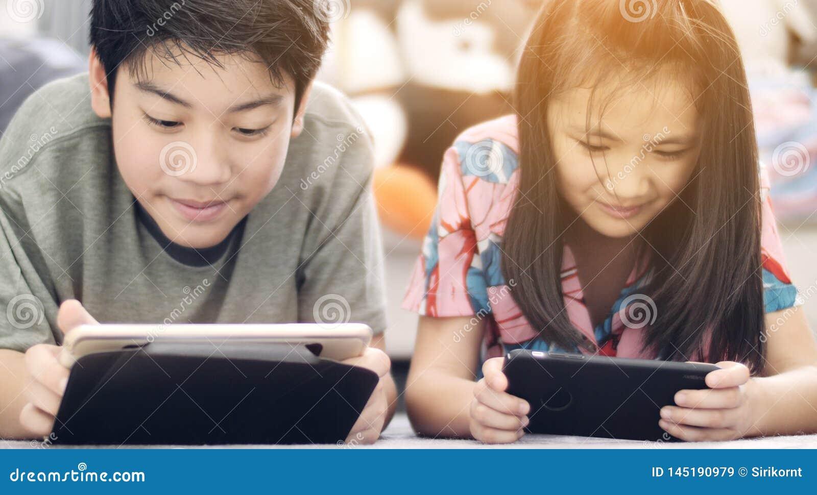 Garçon asiatique et fille jouant le jeu au téléphone portable ainsi que le visage de sourire