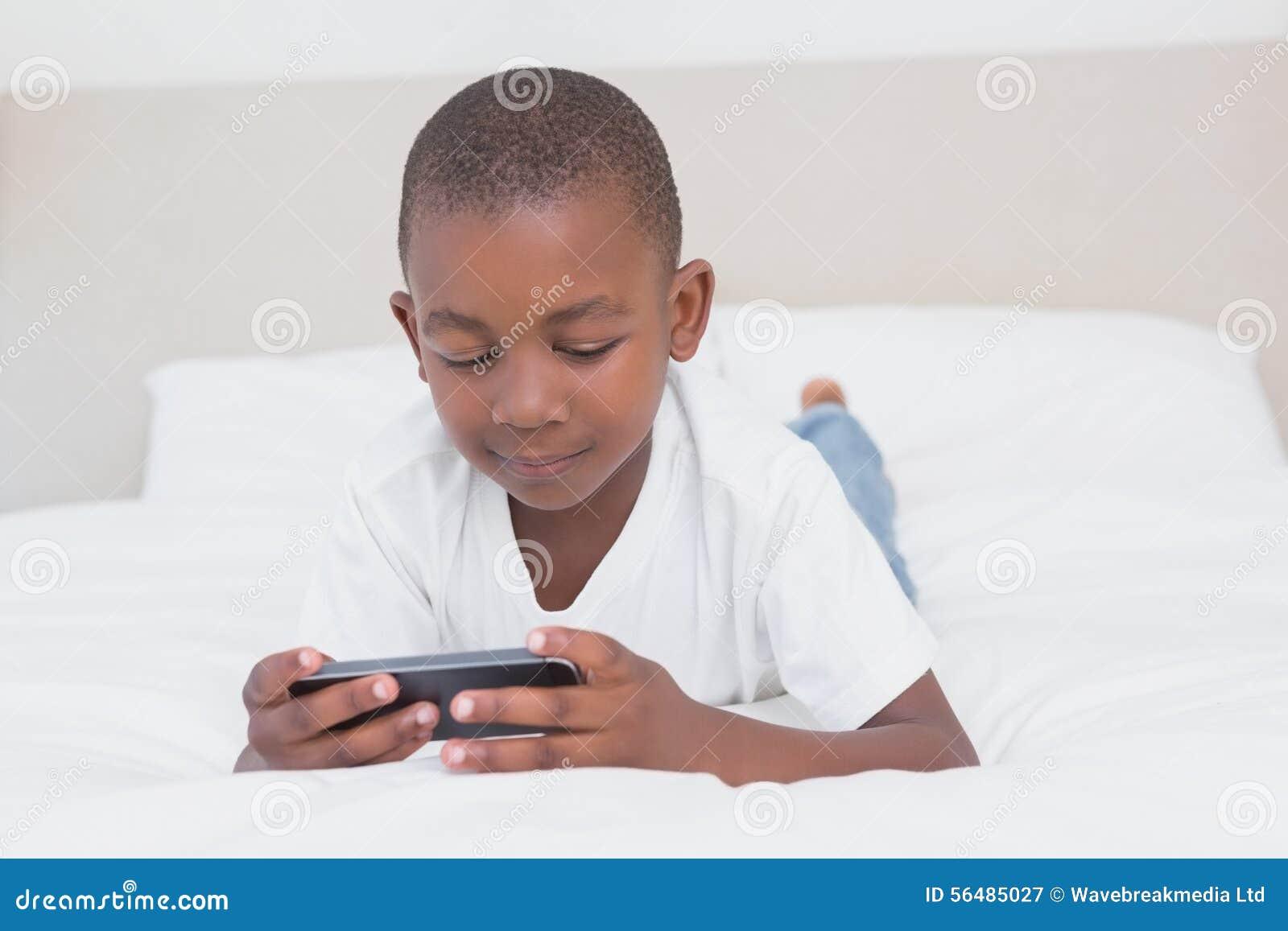 Garçon assez petit à l aide du smartphone dans le lit