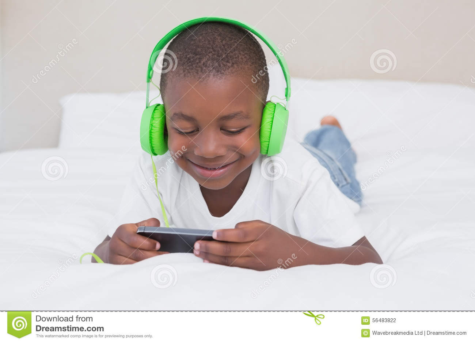 Garçon assez petit employant le smartphone et la musique de écoute dans le lit