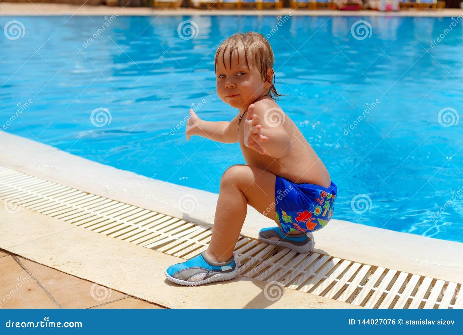 Garçon aux cheveux blonds d enfant près de la piscine