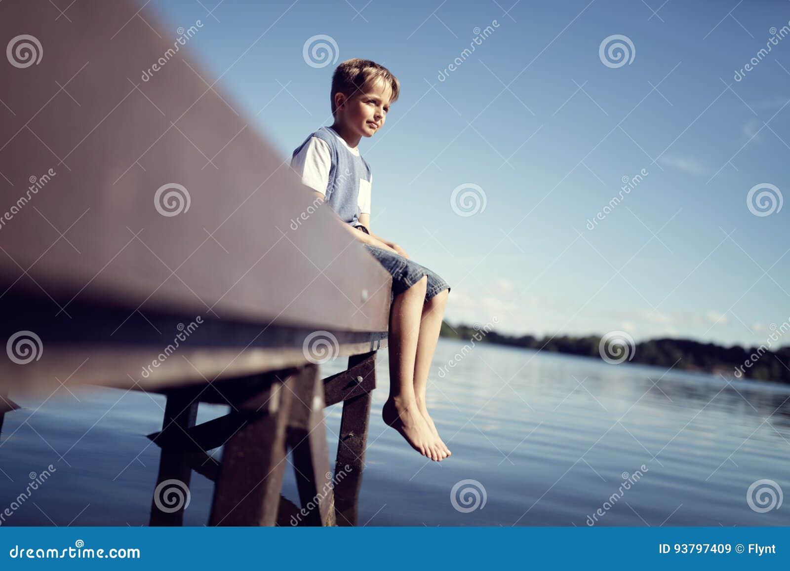 Garçon avec des jambes balançant du pilier