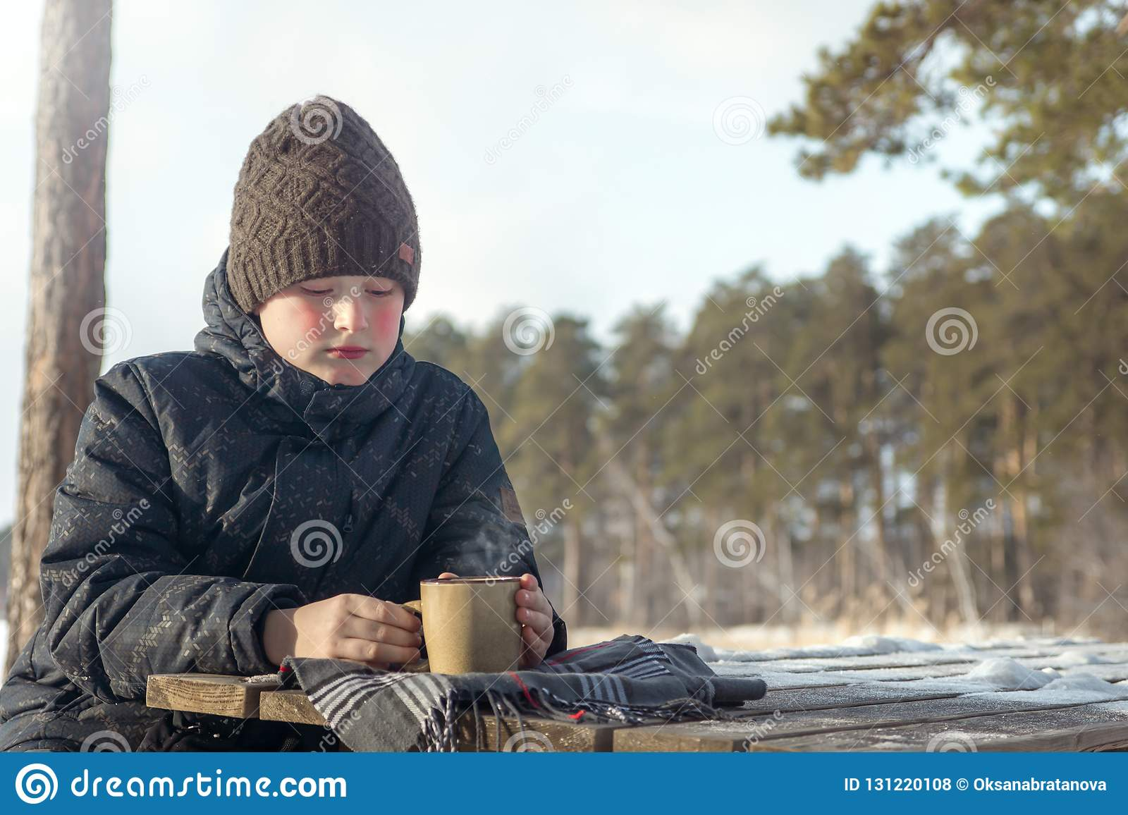 Garçon avec la boisson chaude d hiver extérieure