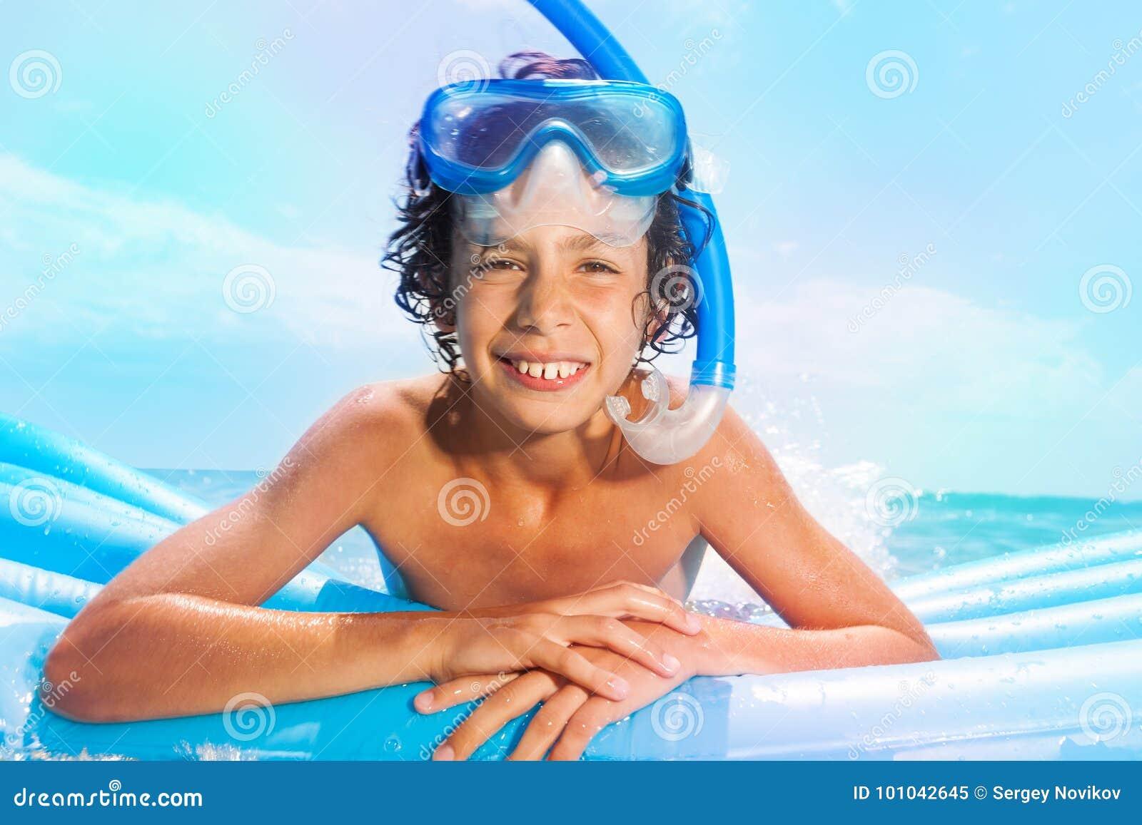 Garçon avec le bain de masque de scaphandre sur des matrass en mer
