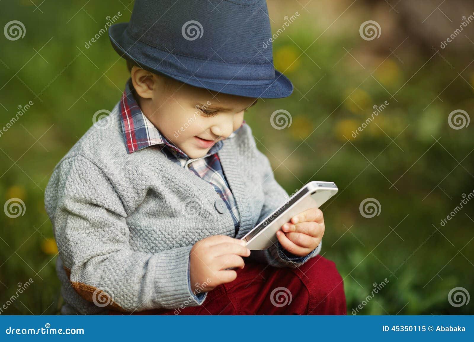 Garçon avec le téléphone se reposant sur l herbe