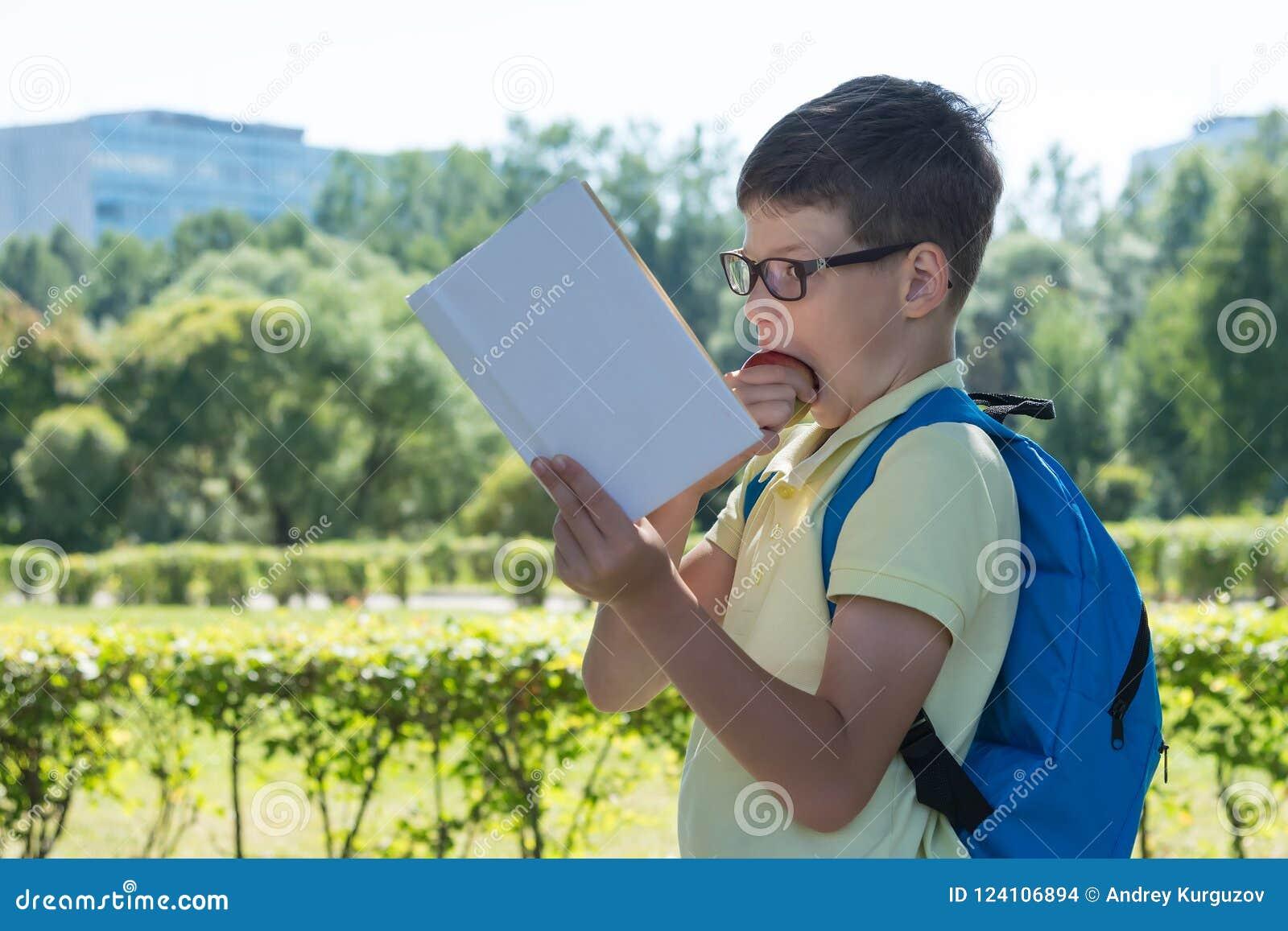 Garçon avec une serviette lisant un livre et mordant une pomme sur la rue