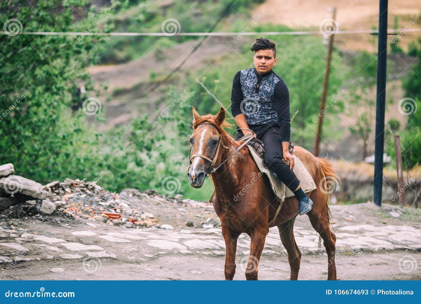 Garçon azéri montant un cheval dans la rue sur la rue de Huseynov de pavé rond, la rue principale du village montagneux de Lahic