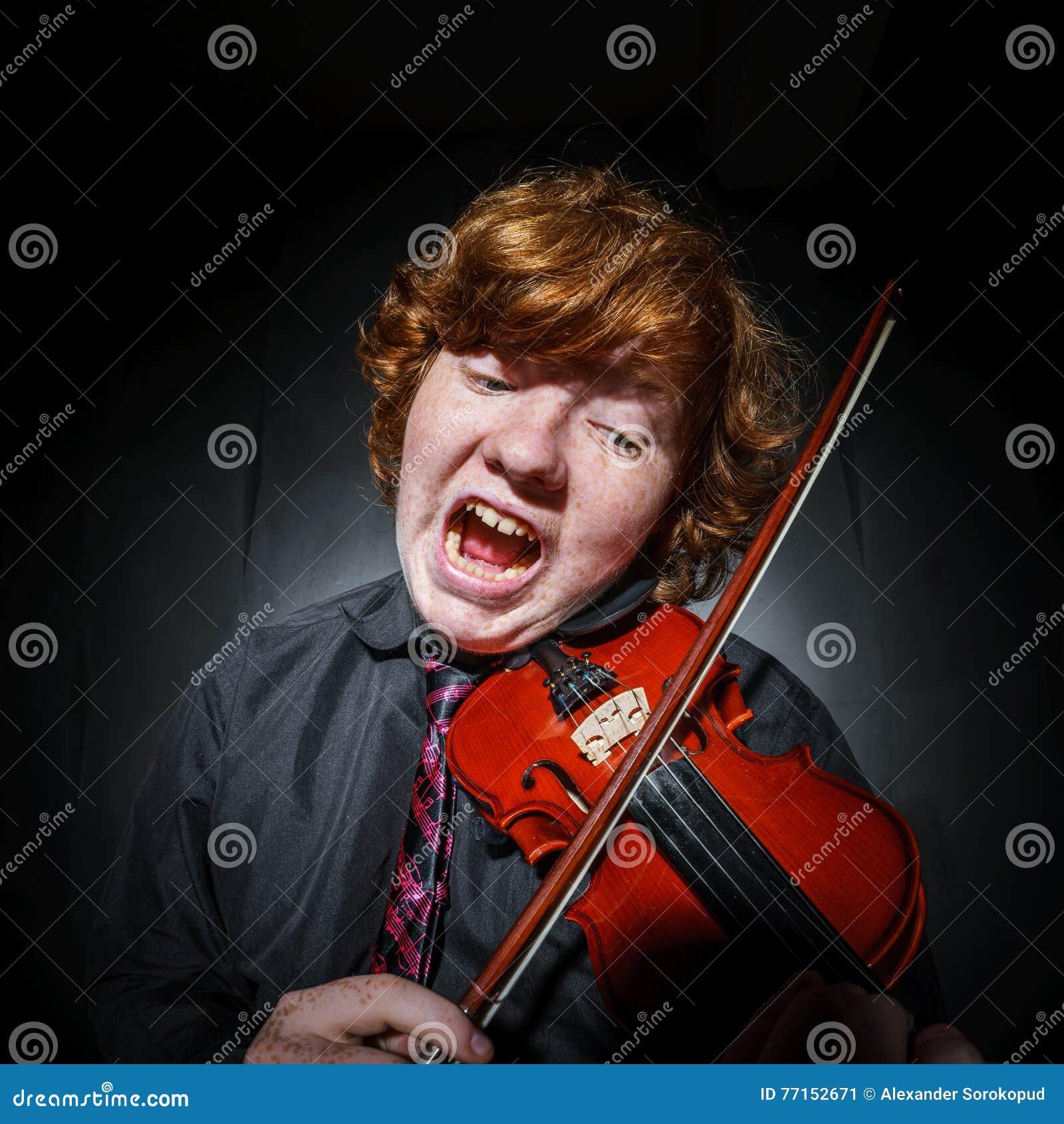 Garçon couvert de taches de rousseur de rouge-cheveux jouant le violon