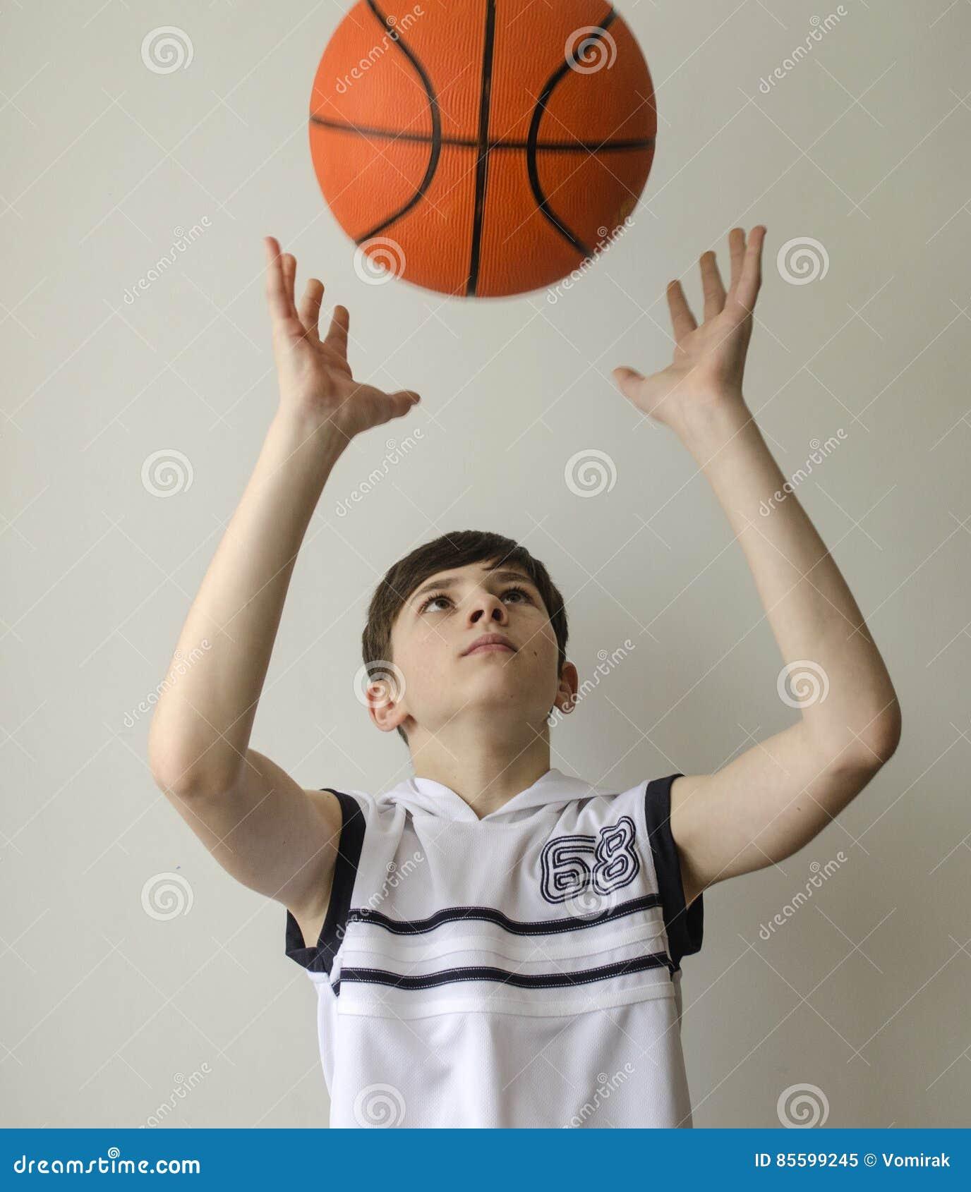 Garçon d adolescent dans une chemise blanche avec une boule pour le basket-ball