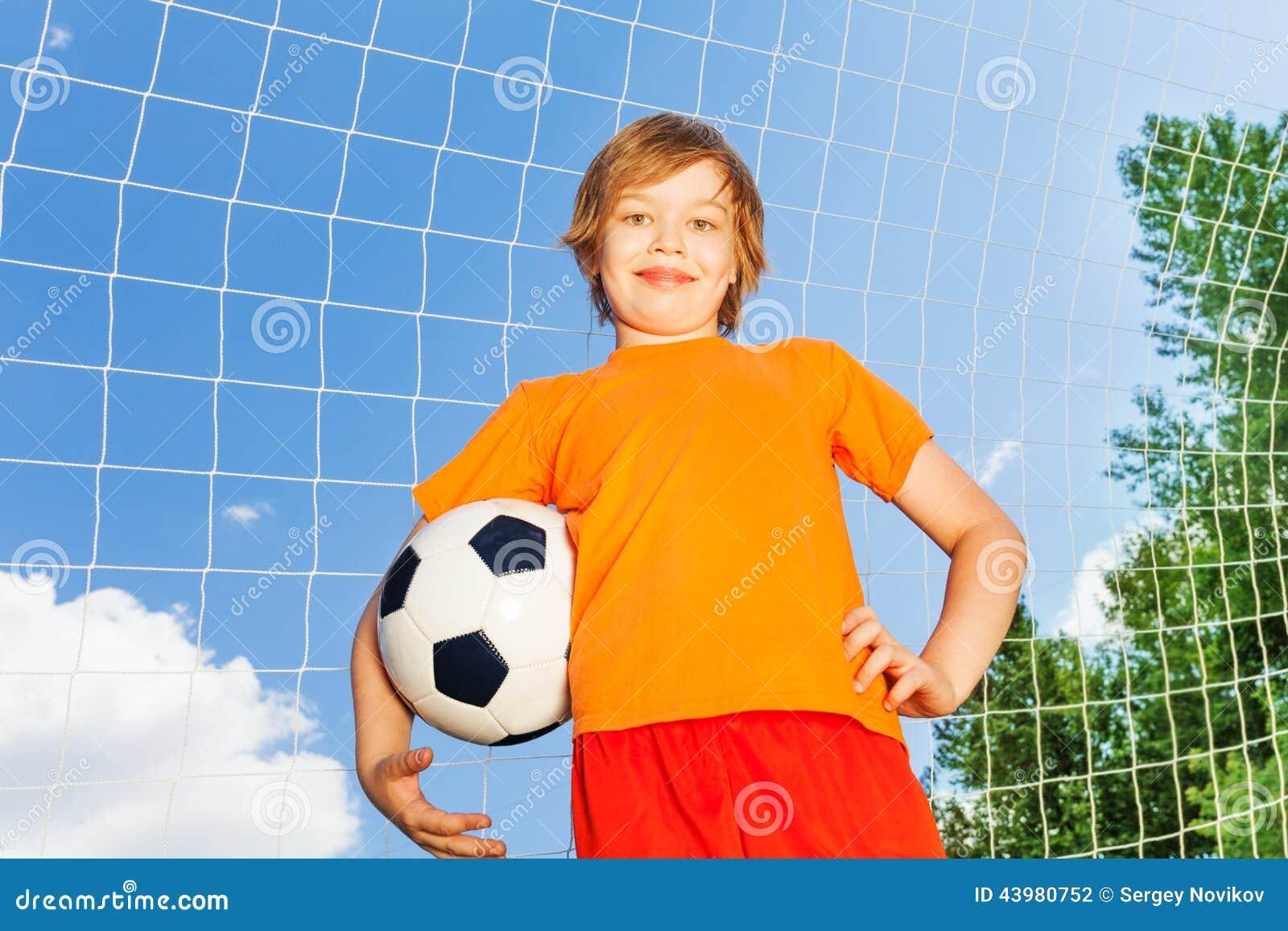 Garçon dans le T-shirt orange avec le football près du boisage