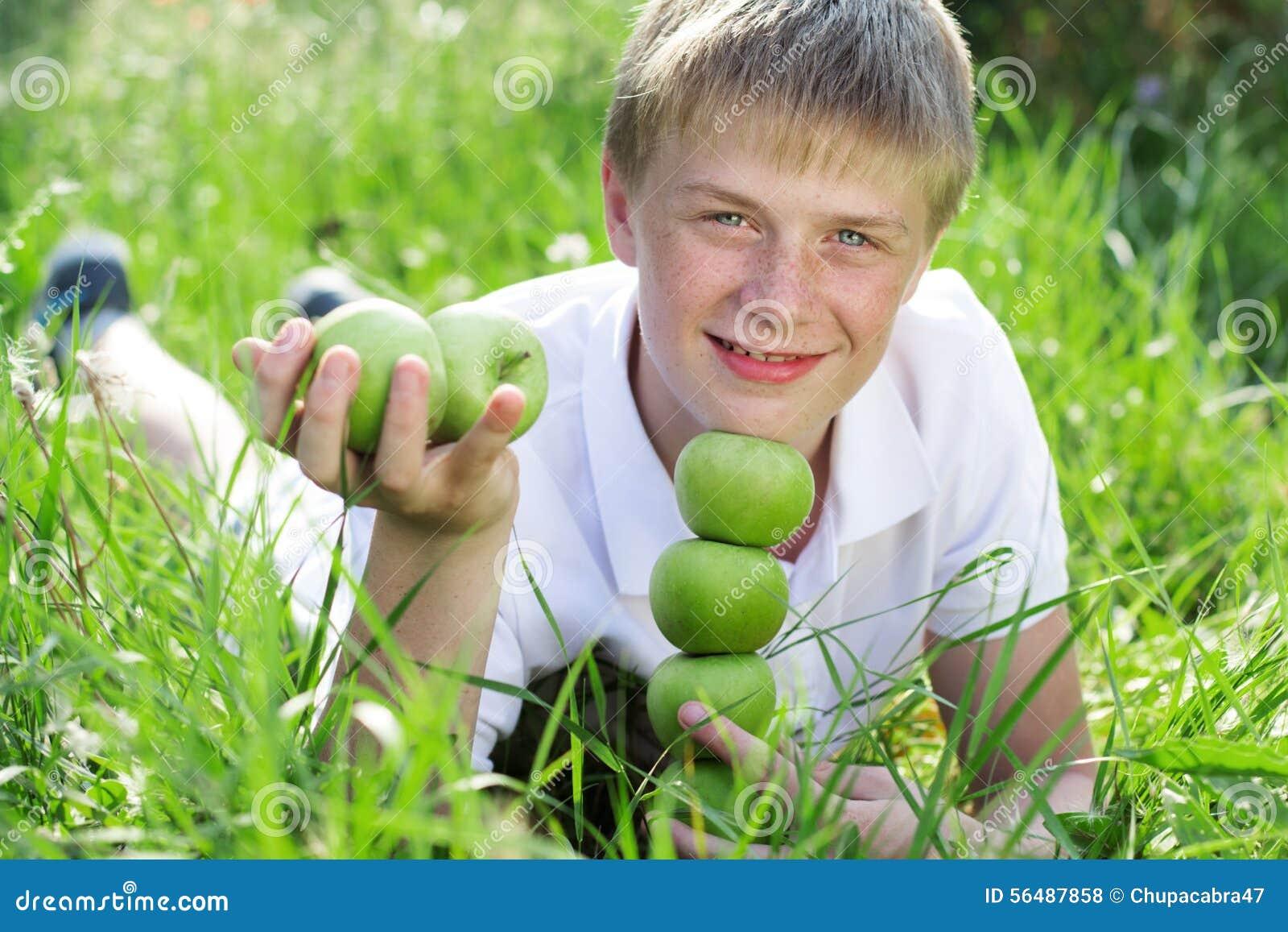 Garçon de l adolescence avec la pyramide des pommes vertes se trouvant dessus