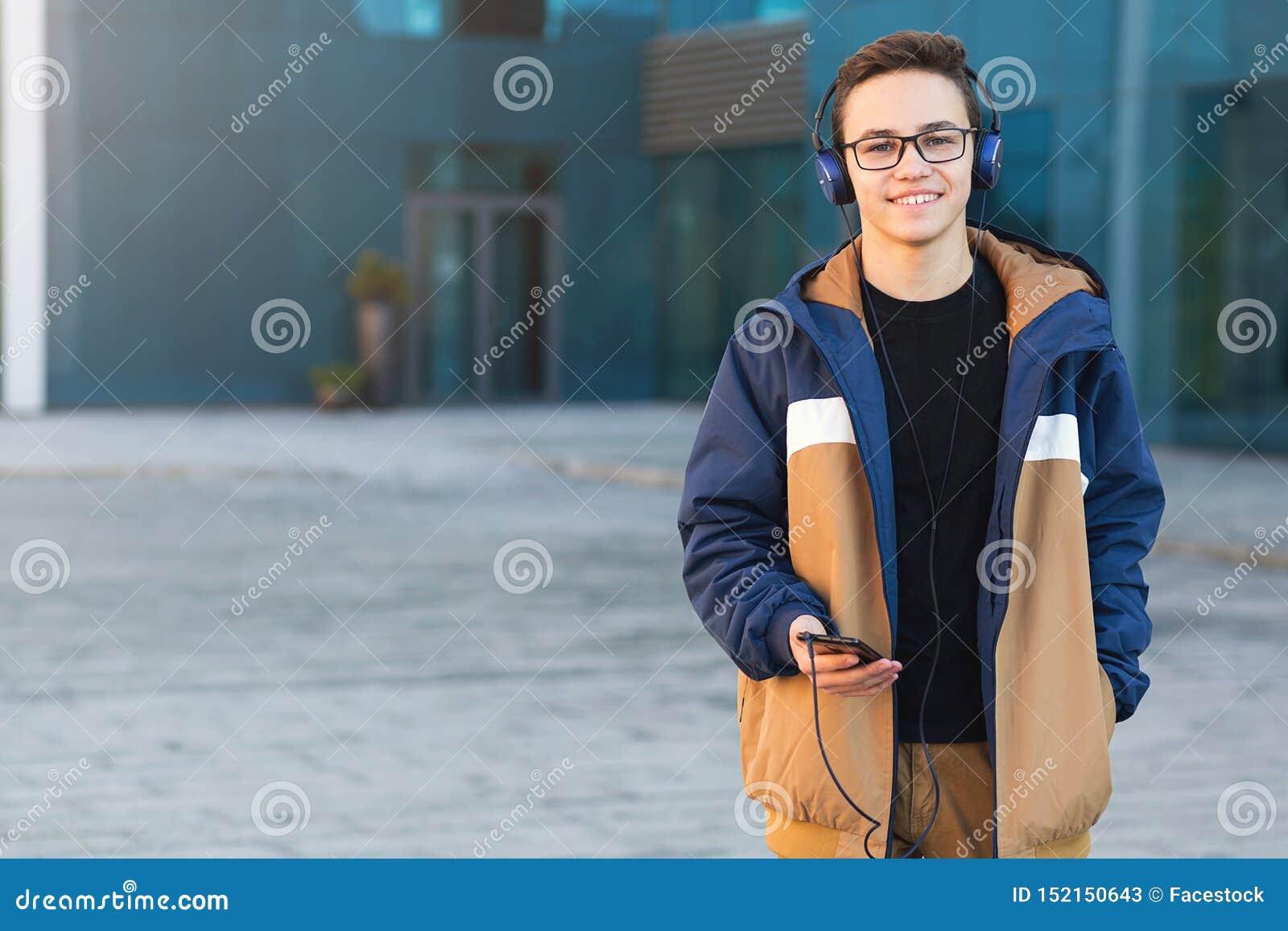 Garçon de l adolescence mignon avec la planche à roulettes dehors, se tenant sur la rue