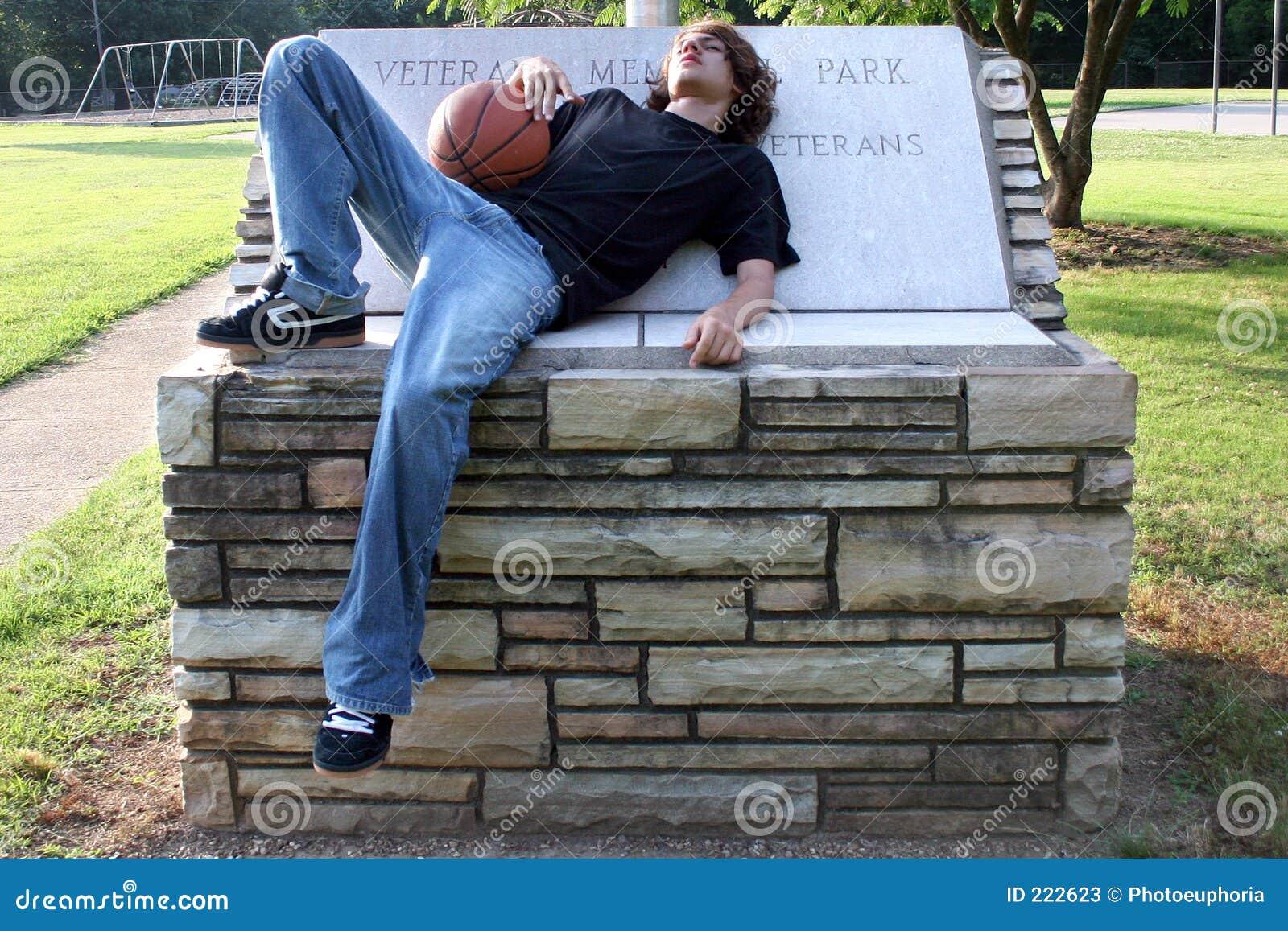 Garçon de l adolescence se reposant après match de basket