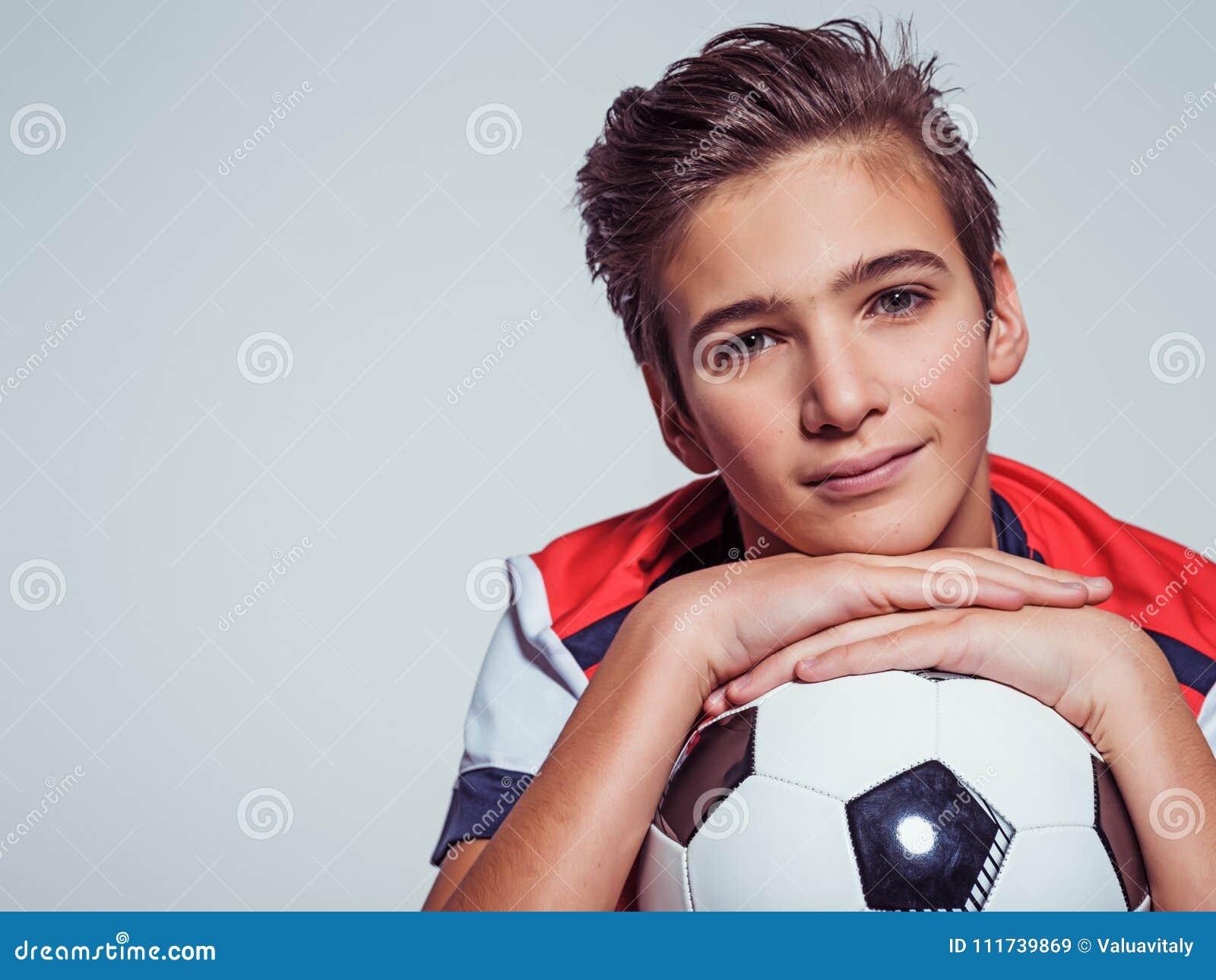 Garçon de l adolescence de sourire dans les vêtements de sport tenant le ballon de football