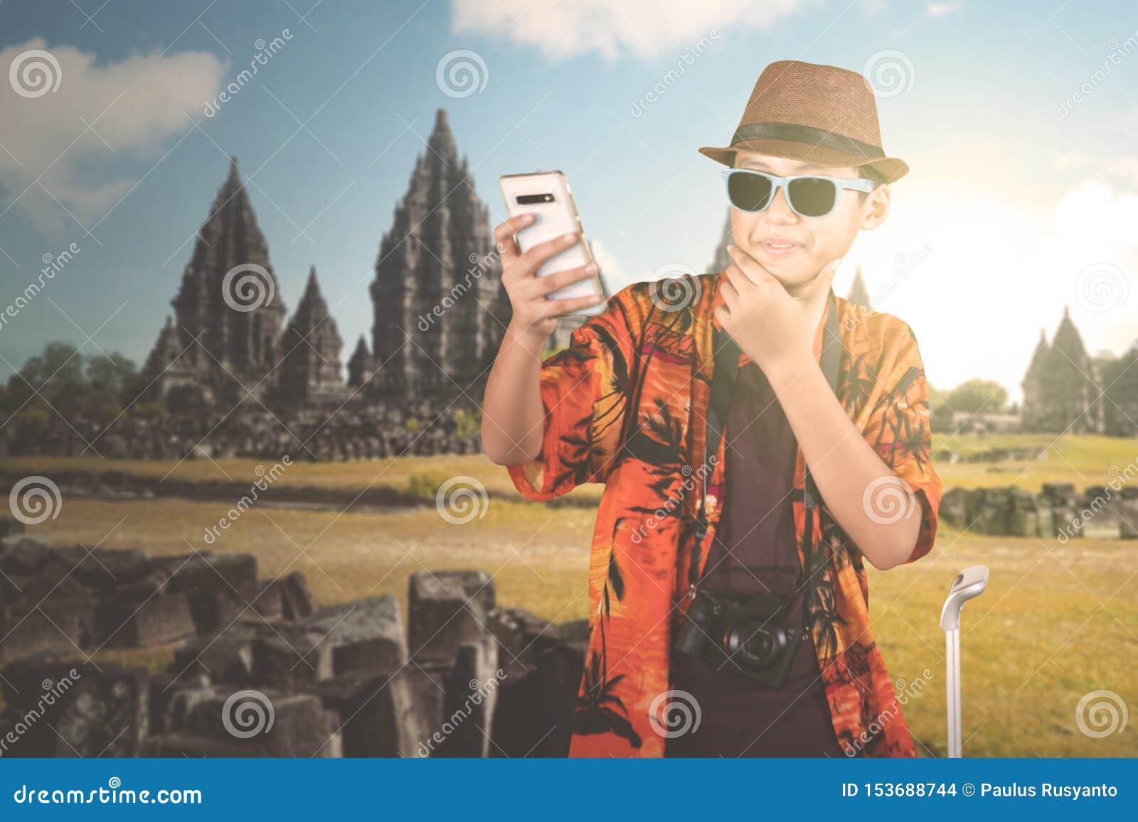 Garçon de la préadolescence prenant la photo près du temple de Prambanan