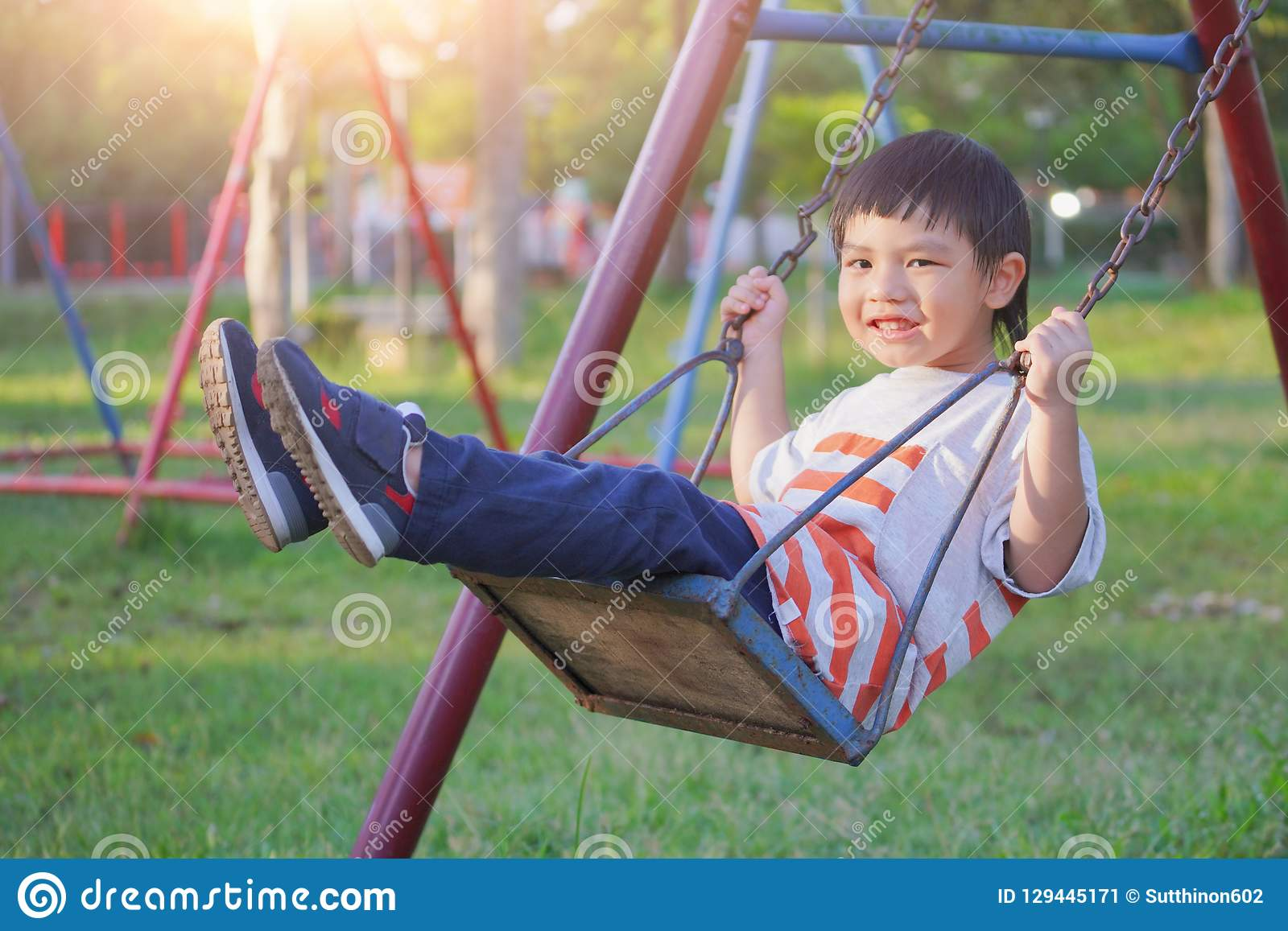 Garçon de sourire balançant sur une corde à un terrain de jeu