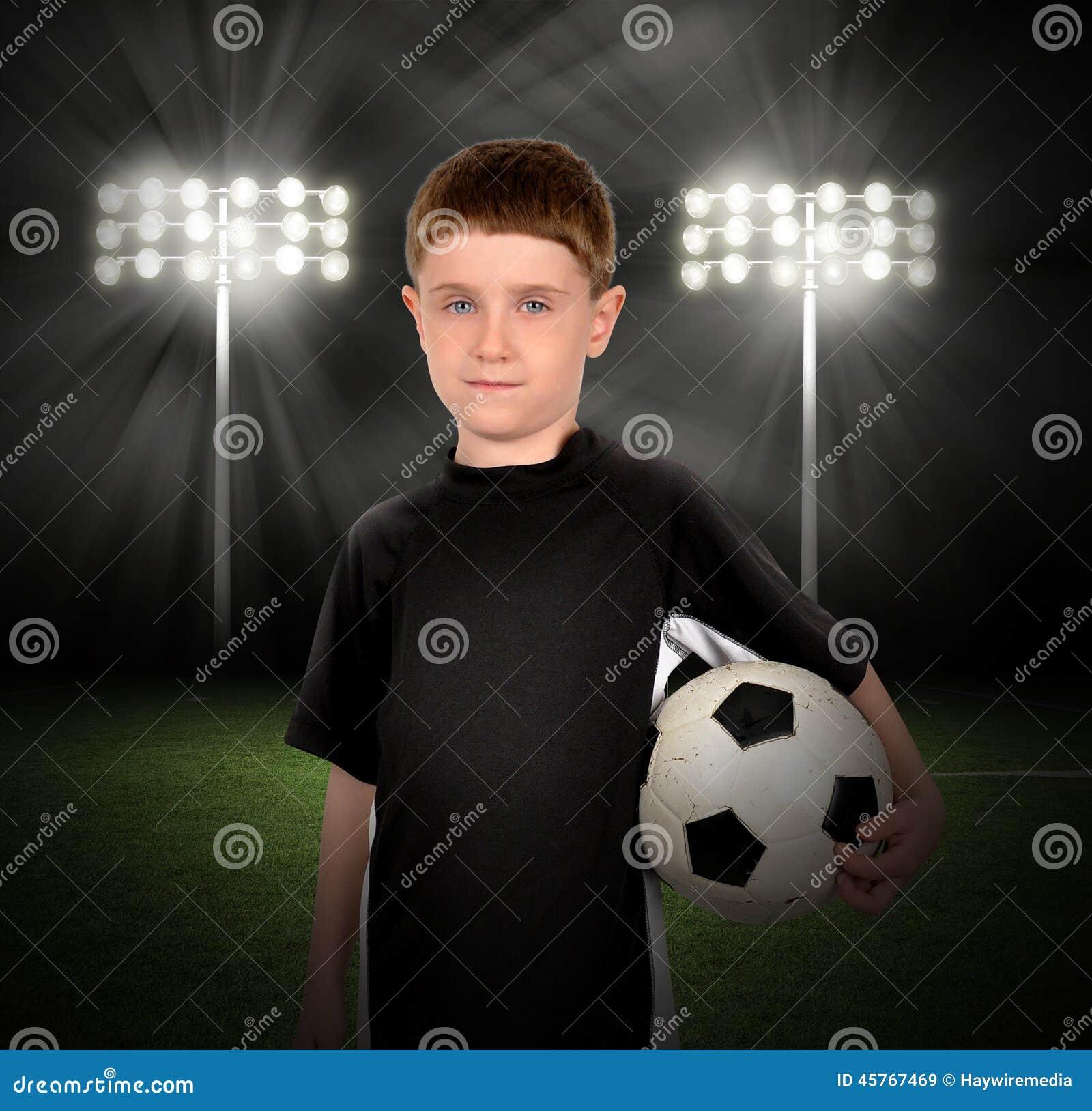 Garçon du football tenant la boule dans le stade