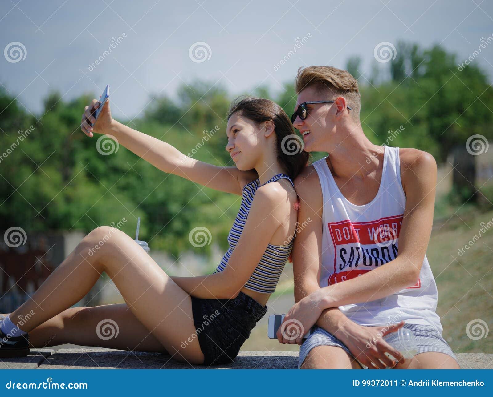 Garçon et fille de sourire heureux sur un fond de parc Ami et amie prenant des photos Concept progressif de la jeunesse