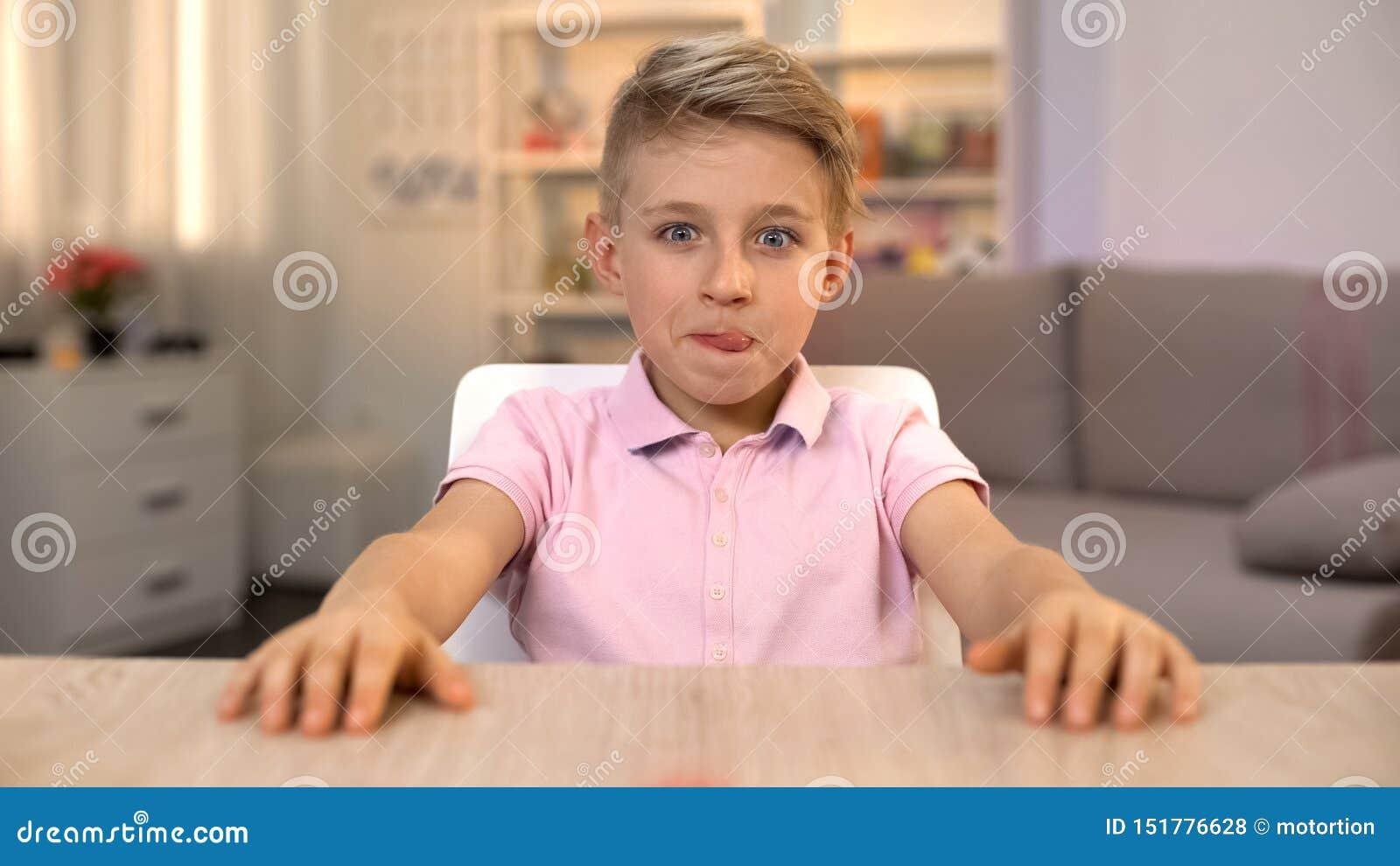 Garçon heureux léchant des lèvres et regardant la nourriture savoureuse sur la table de cuisine, nutrition