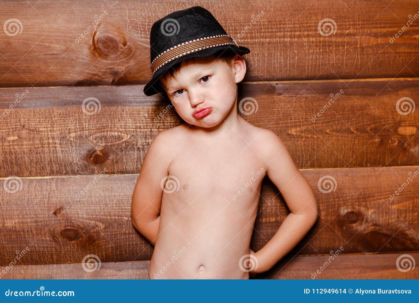 Garçon irrité dans le chapeau sur le fond du mur en bois