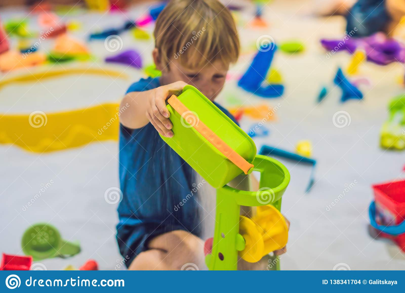 Garçon jouant avec le sable dans l école maternelle Le développement du concept fin de moteur Concept de jeu de créativité