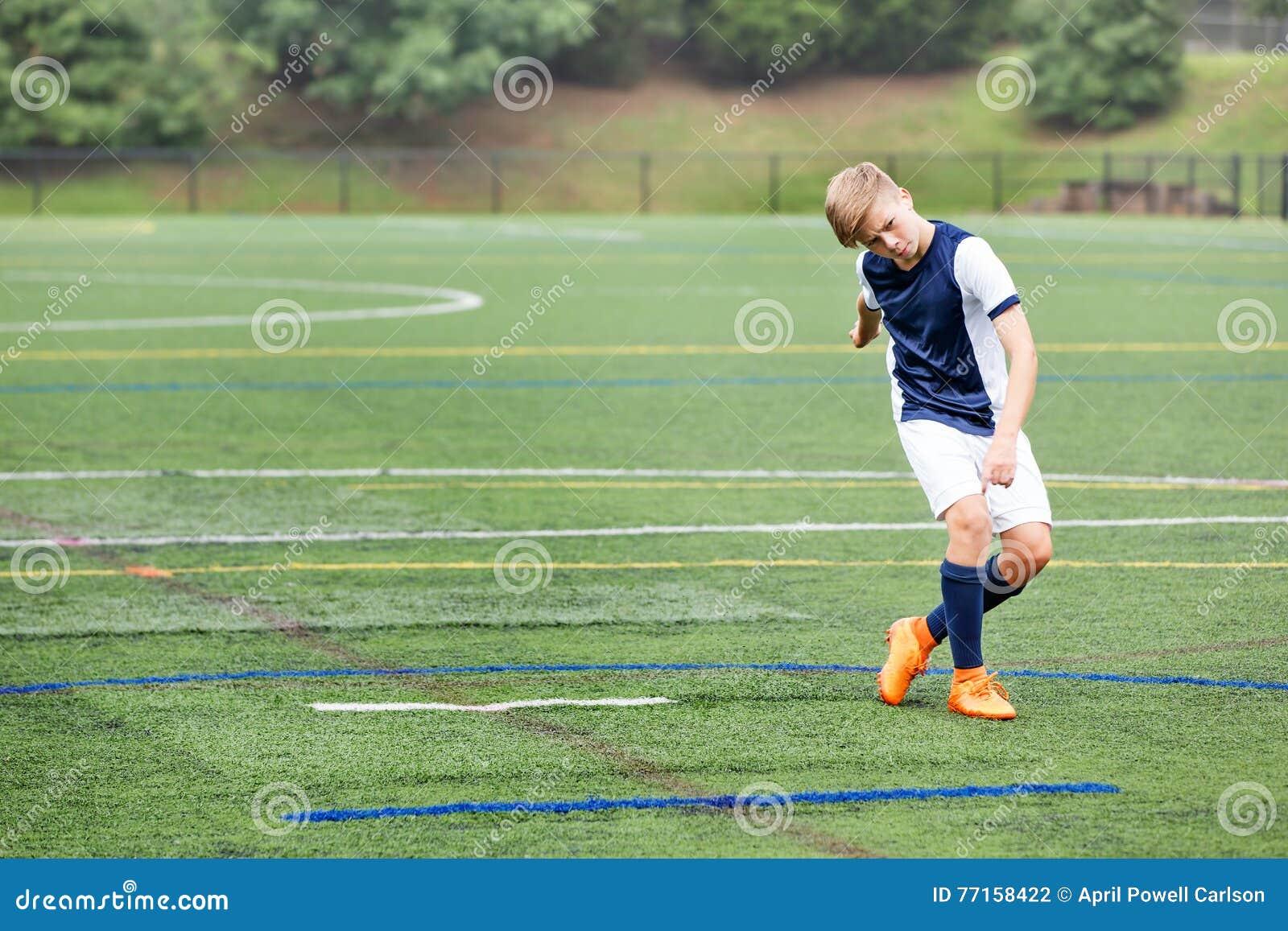 Garçon jouant le football - a juste donné un coup de pied la boule
