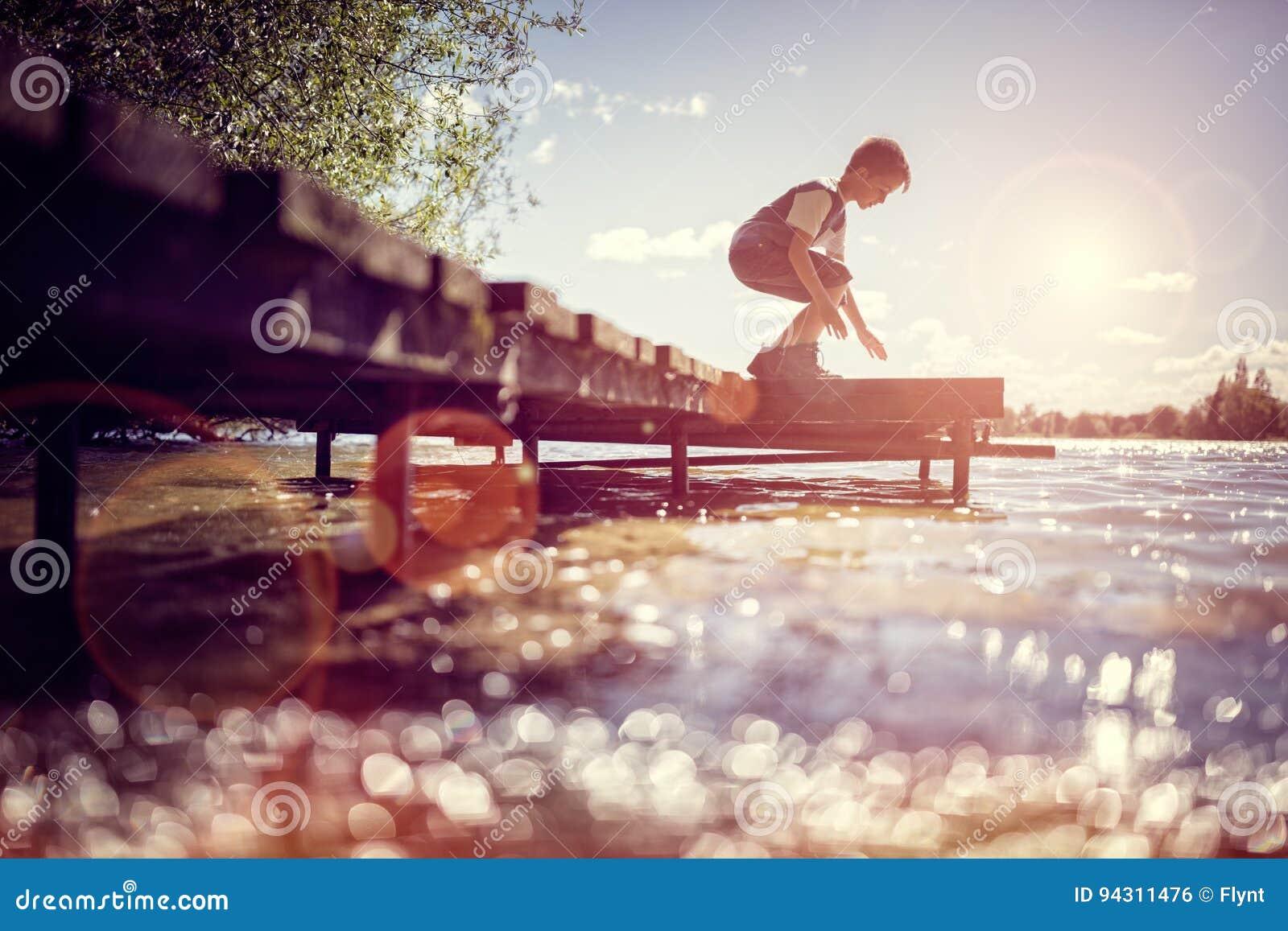 Garçon jouant sur un pilier par le lac des vacances d été