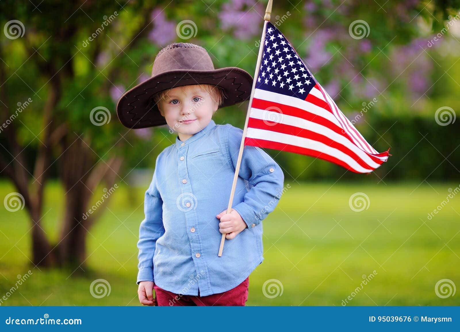 Garçon mignon d enfant en bas âge tenant le drapeau américain en beau parc