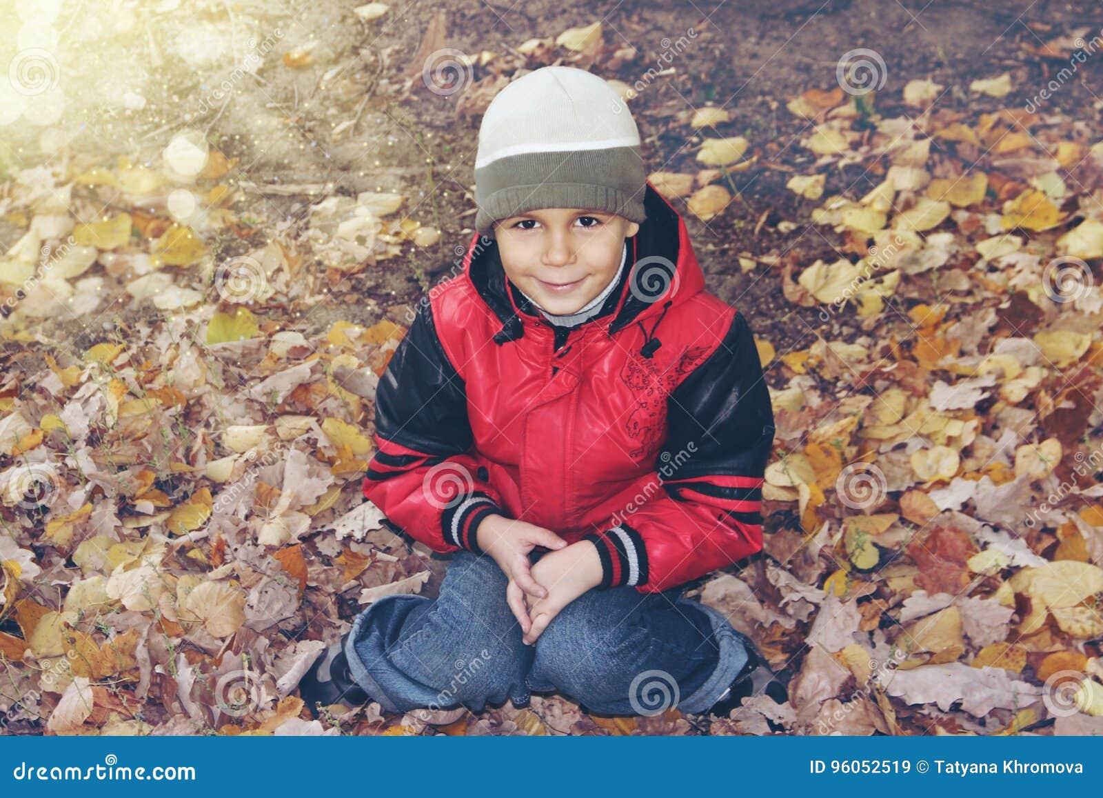 Garçon mignon dans des lames d automne