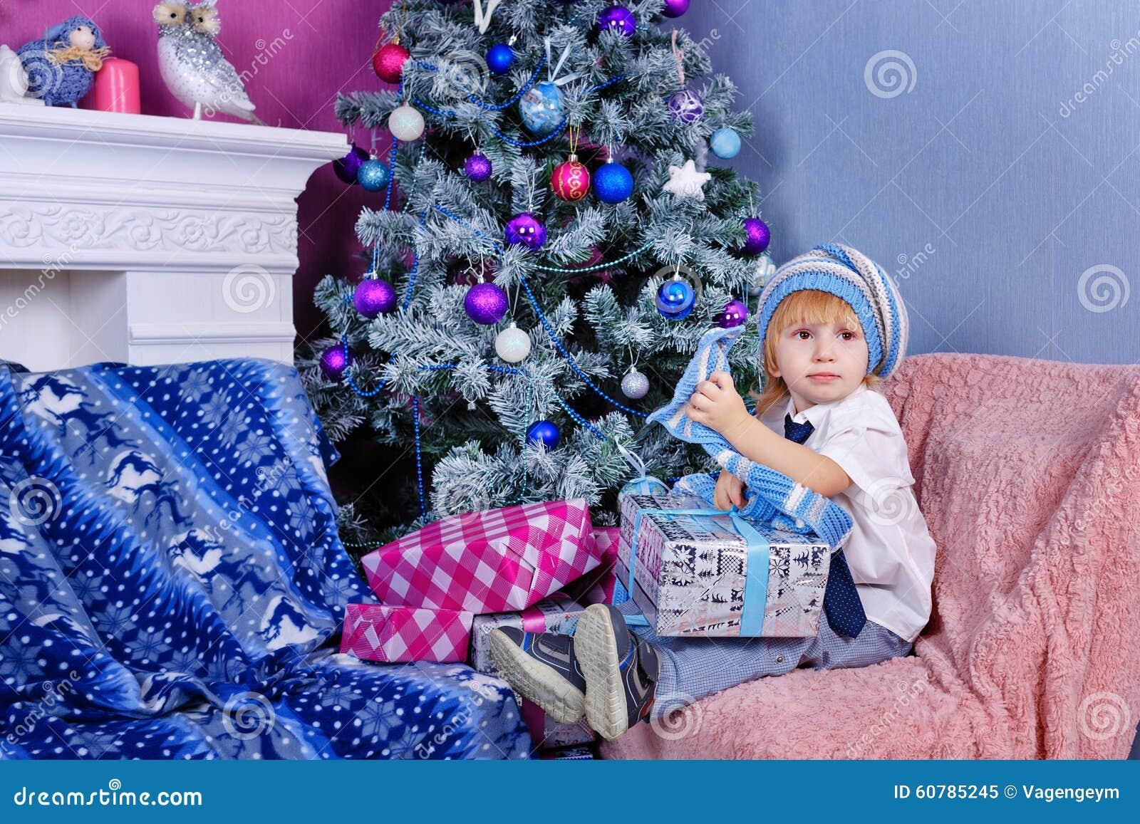 Garçon mignon dans le chapeau déballant des cadeaux de Noël