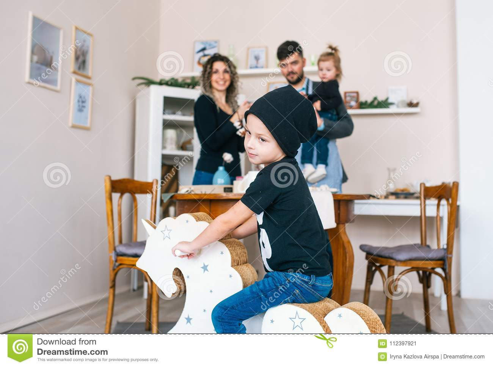 Garçon mignon dans le chapeau noir et le T-shirt basculant sur le cheval en bois Petit enfant ayant l amusement avec le jouet de