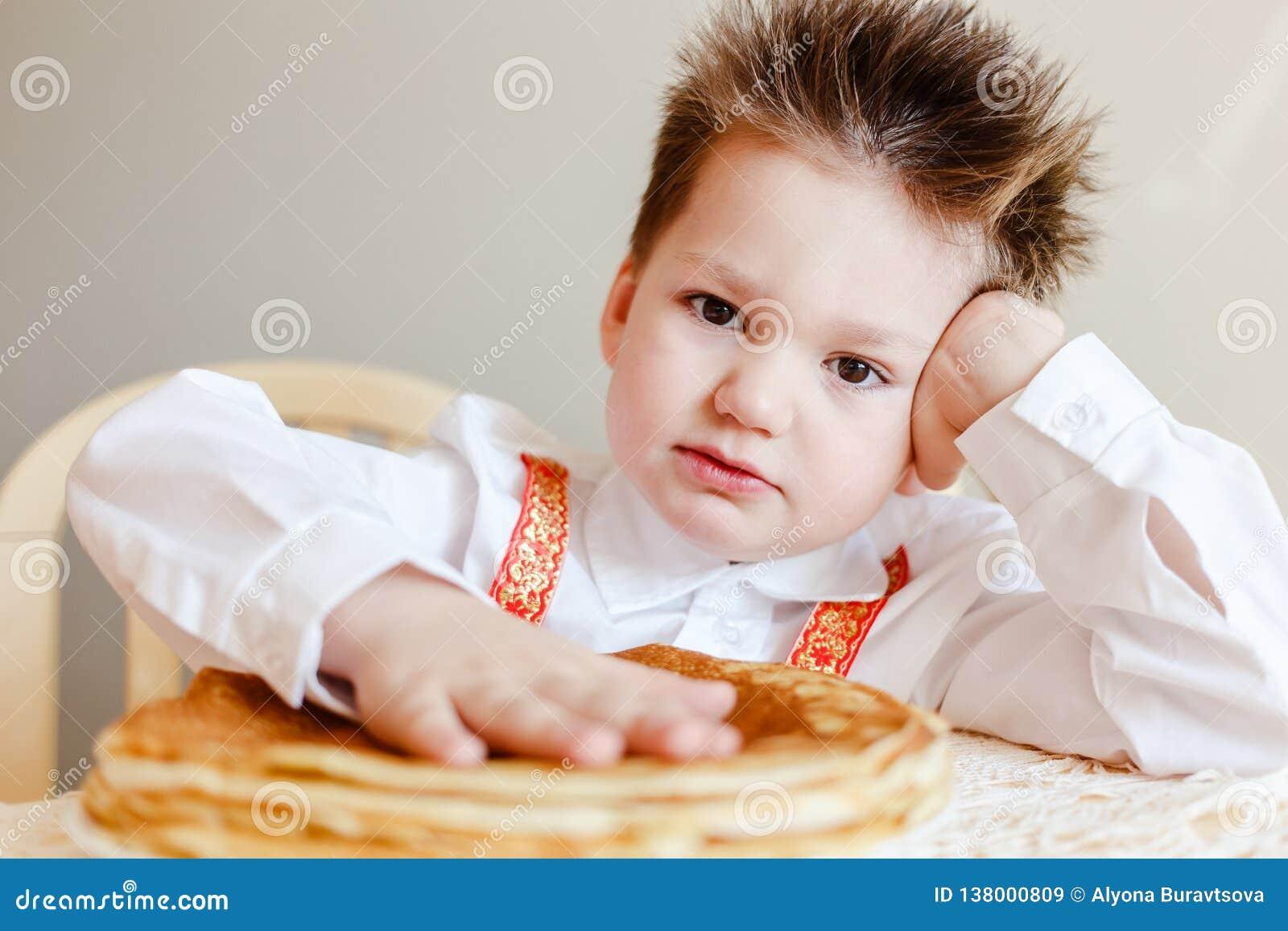 Garçon mignon et un plat des crêpes