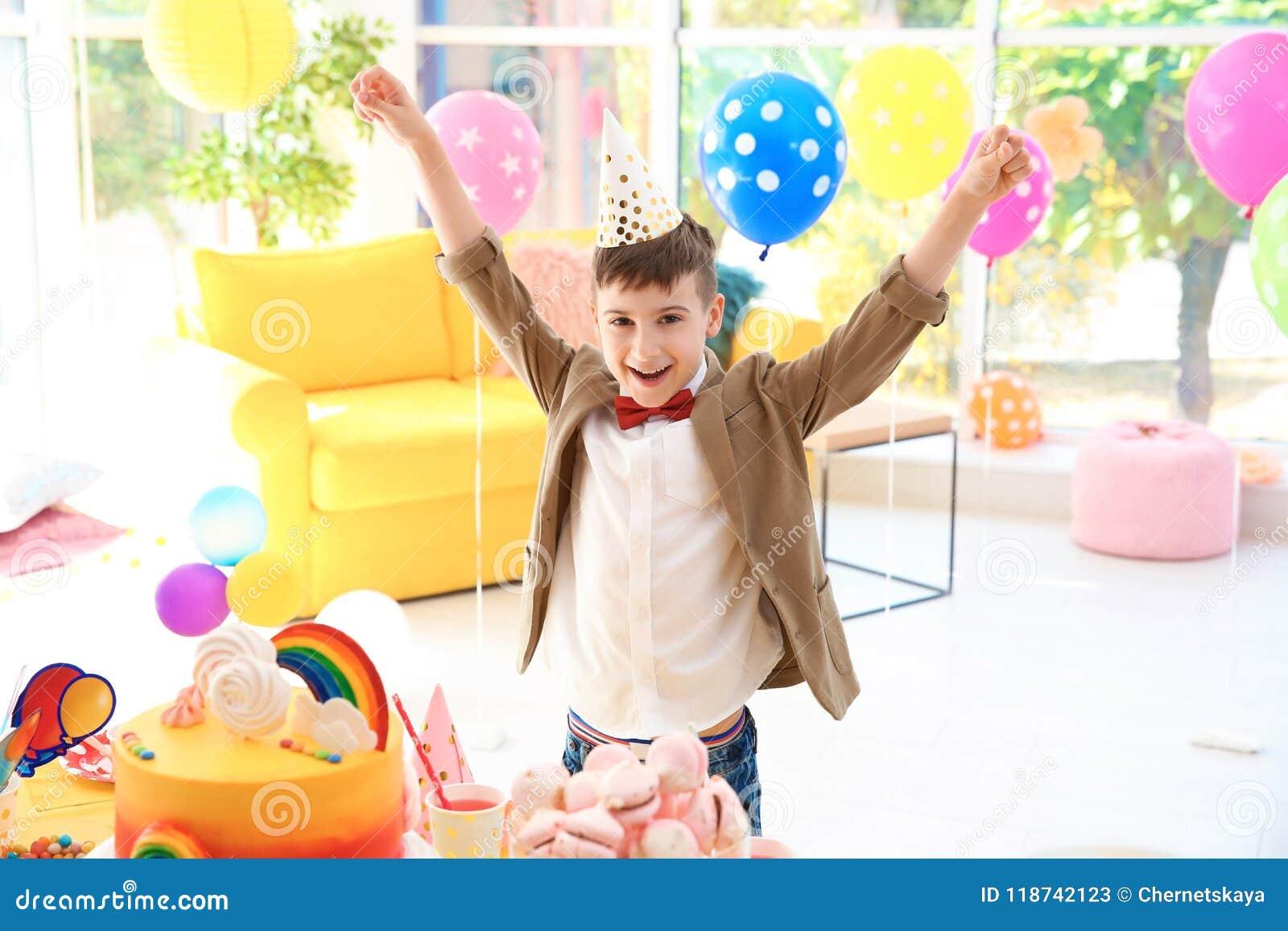 Garçon mignon près de table avec des festins à la fête d anniversaire à l intérieur