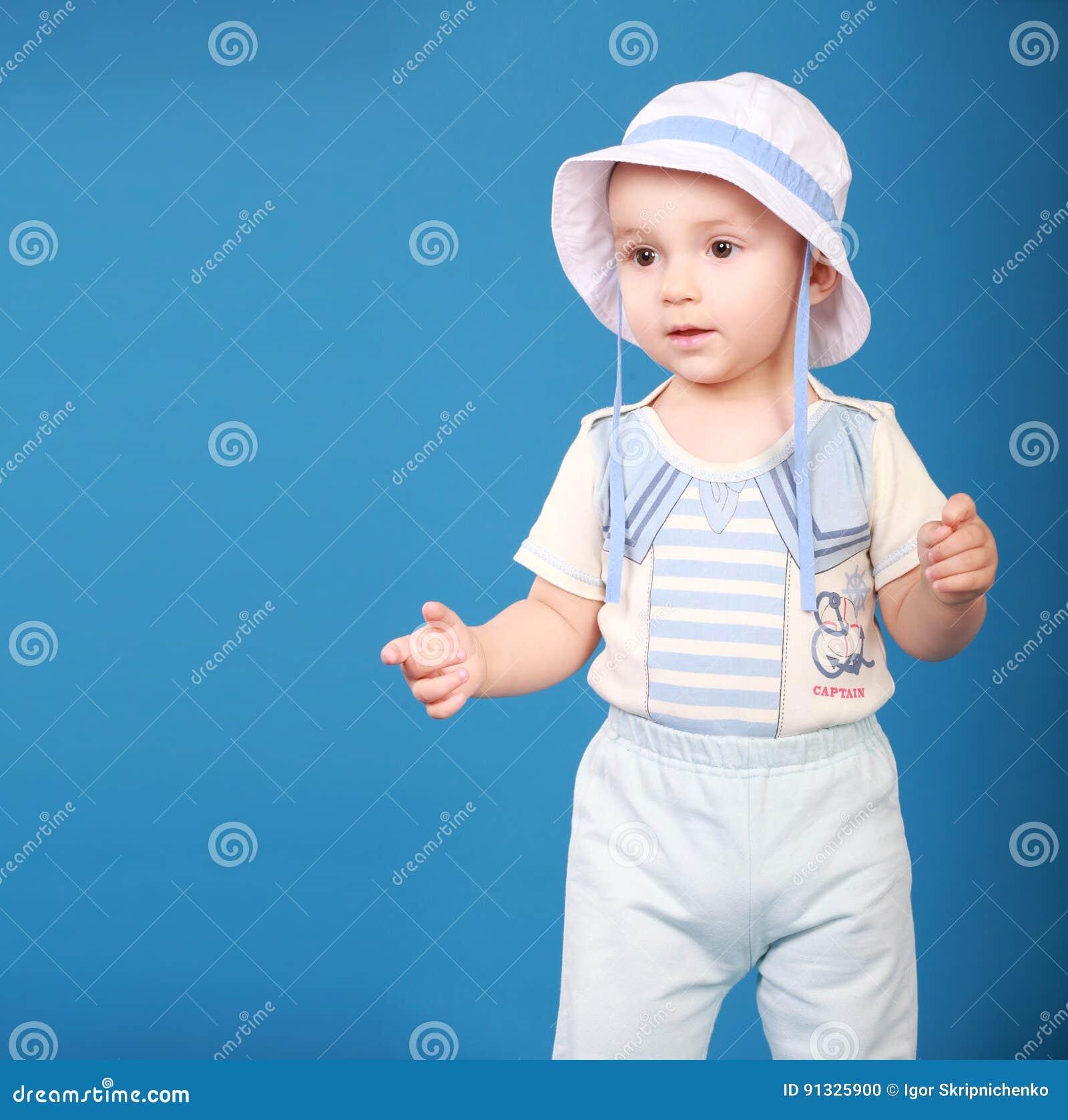 Garçon mignon se tenant sur un fond bleu portant un marin