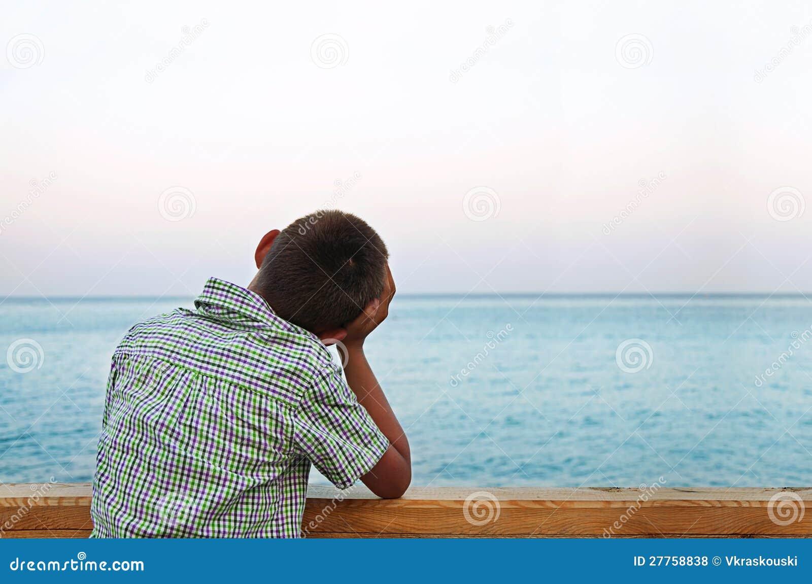 Garçon regardant la mer dans le coucher du soleil