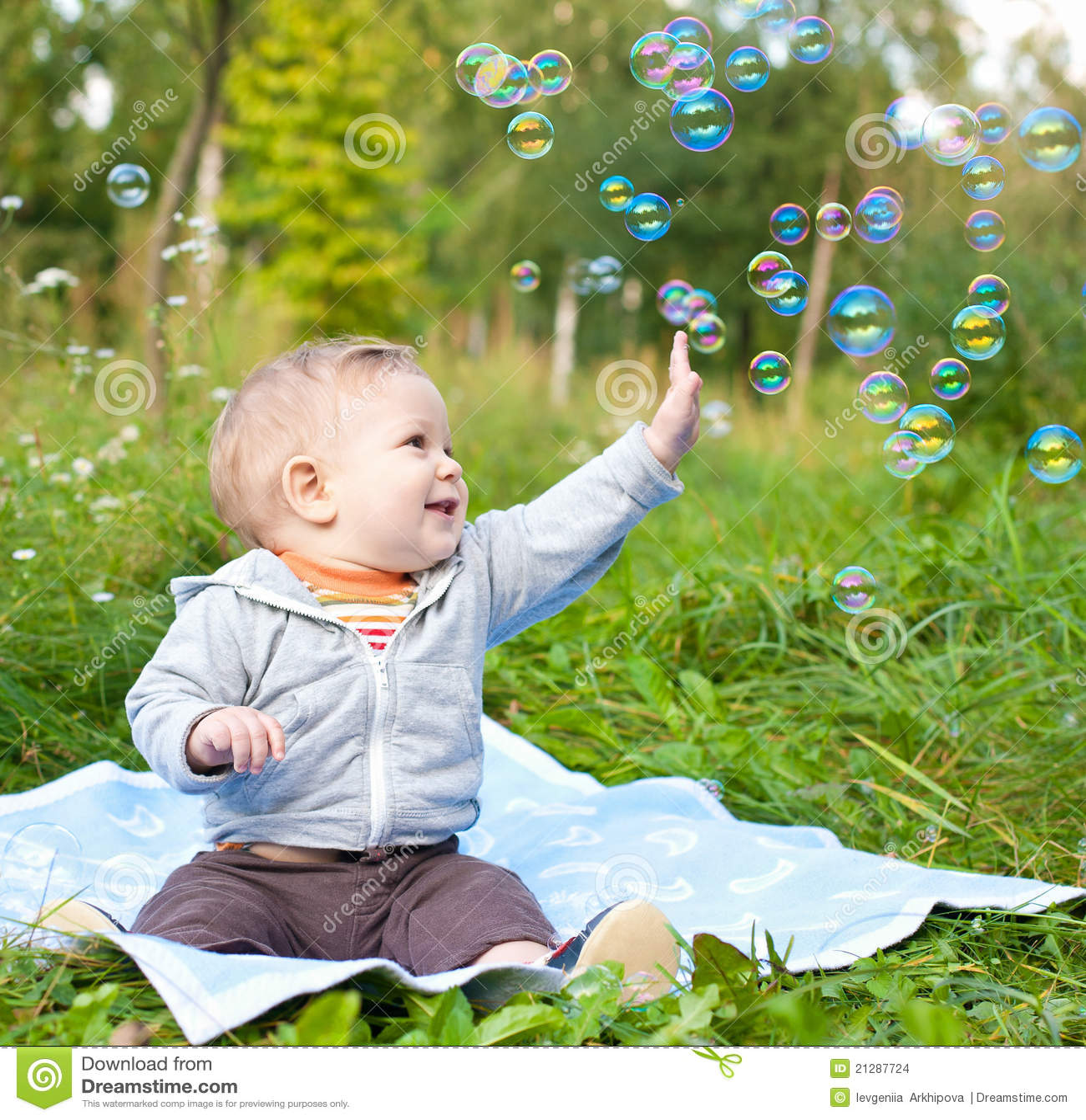 Garçon s asseyant sur l herbe jouant avec des bulles de savon