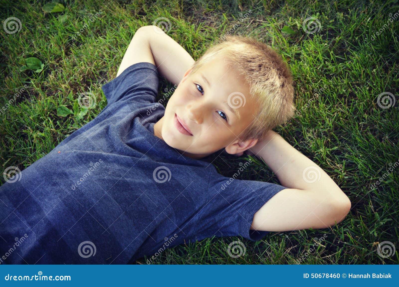 Garçon se situant dans l herbe