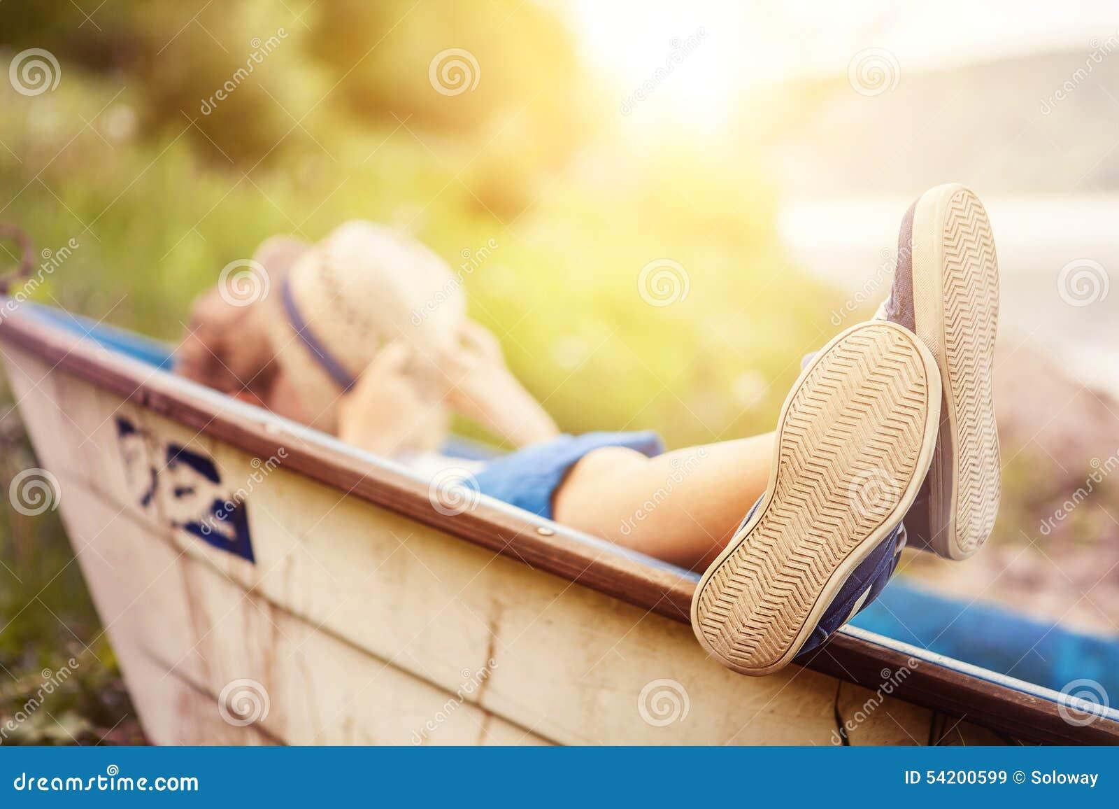Garçon se situant dans le vieux bateau dans la fin de côte de lac vers le haut de l image